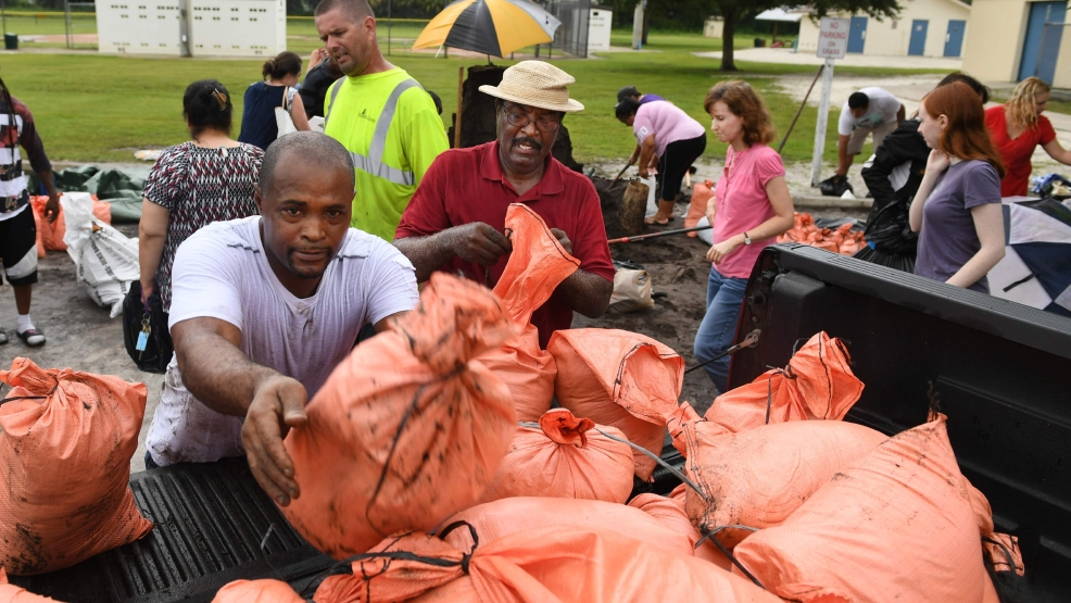 James Byrd, left, and Richard Clark, right, load their sandbags in a truck Wednesday afternoon at Newtown Estates Rec Center in Sarasota, Florida, as they prepare for Hurricane Irma. The each got their ten bags before Sarasota County ran out of sandbags for residents. The county still has plenty of dirt but people must bring and fill their own bags. A new shipment of sandbags is expected Thursday. [Herald-Tribune staff photo / Mike Lang]