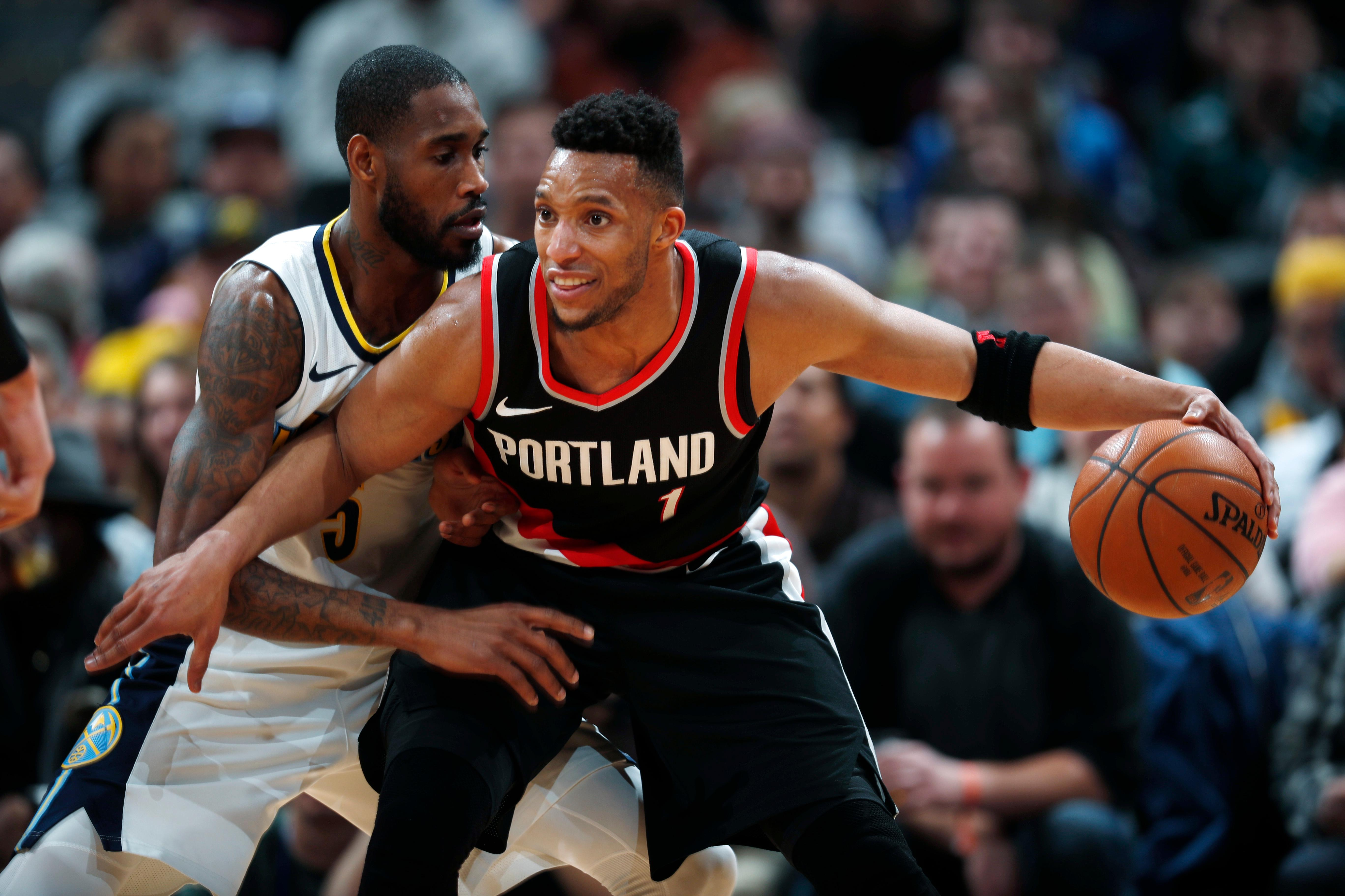 Portland Trail Blazers guard Evan Turner, right, looks to pass the ball as Denver Nuggets guard Will Barton defends in the first half of an NBA basketball game Monday, Jan. 22, 2018, in Denver. (AP Photo/David Zalubowski)