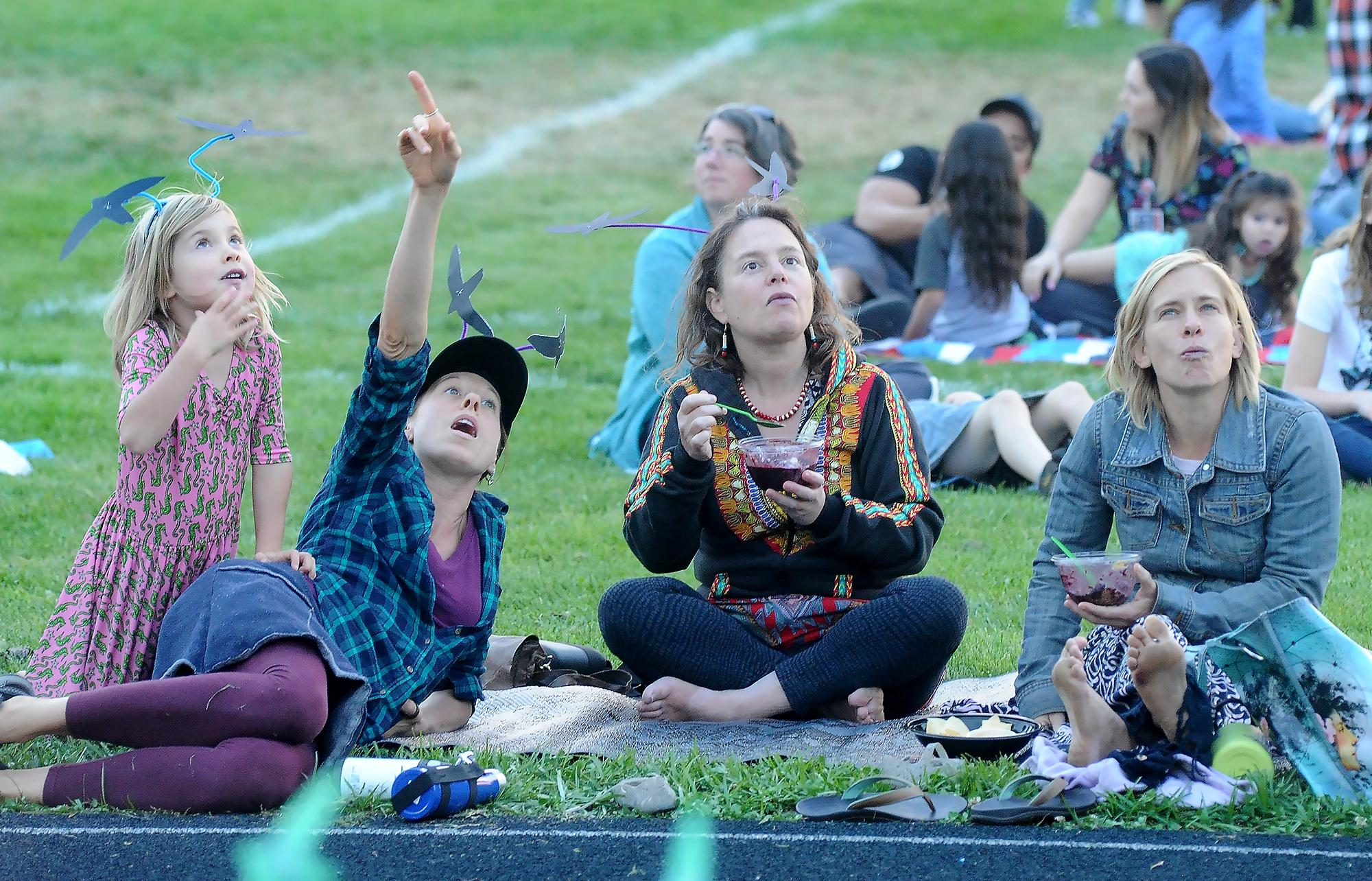 Madeleine Fox, 5, (left), Marisa Knesel, Nabha Goldfeder and Kate Fox react as they watch thousands of swifts fly into a chimney Tuesday night at Hedrick Middle School. Photo by Denise Baratta