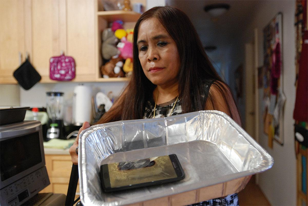 Dee Decasa holds her replacement Galaxy Note 7 smartphone in an aluminum pan at her home in Honolulu on Monday, Oct. 10, 2016, one day after the phone released smoke and sizzled. Samsung said it is halting sales of the Galaxy Note 7 after a spate of fires involving new devices that were supposed to be safe replacements for recalled models. (AP Photo/Audrey McAvoy)
