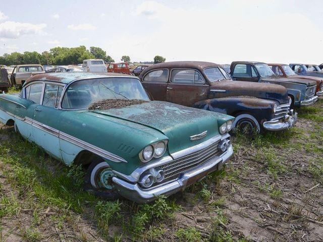 A 1958 Chevrolet Biscayne sits next to a 1947 Chevy and other vehicles in the field on the family farm near the former Lambrecht Chevrolet car dealership.