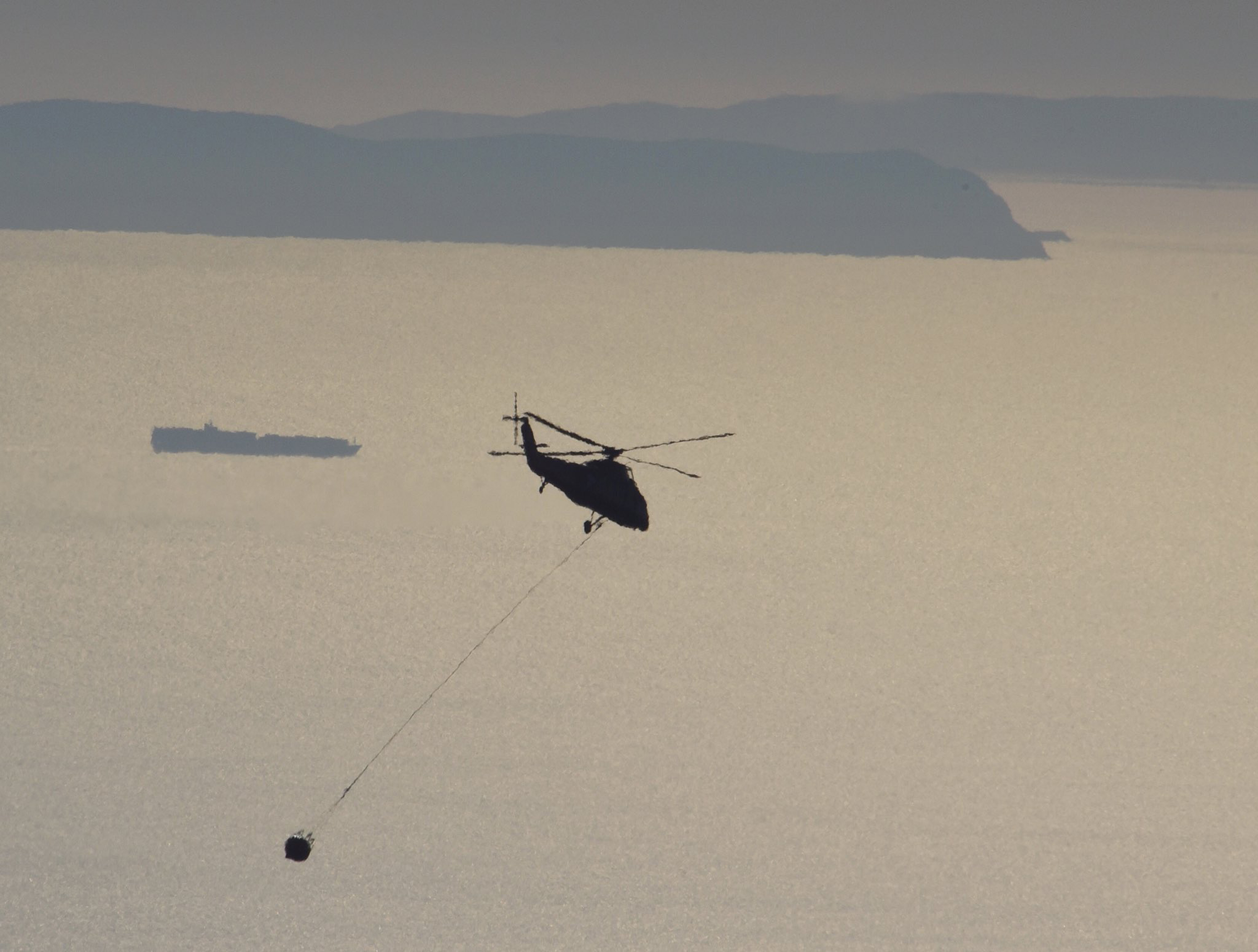 In this photo provided by the Santa Barbara County Fire Department, a pilot takes his firefighting helicopter back to fill its bucket with water while working near Gibraltar Road in Santa Barbara, Calif., Tuesday, Dec. 19, 2017. In the distance, the cargo ship Ever Envoy transits the Santa Barbara Channel with Santa Cruz and Santa Rosa Island behind. Officials estimate that the Thomas Fire will grow to become the biggest in California history before full containment, expected by Jan. 7. (Mike Eliason/Santa Barbara County Fire Department via AP)
