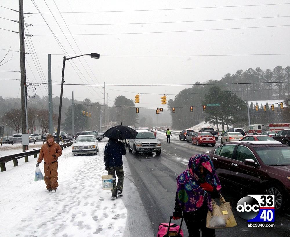 Stranded motorists walk along Highway 31 near Riverchase Parkway during a winter storm, Tuesday, January 28, 2014.