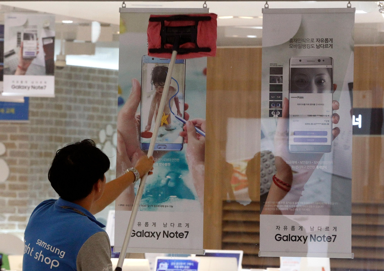 A worker cleans a window as posters of Samsung Electronics Galaxy Note 7 smartphone are displayed at the company's shop in Seoul in Seoul, South Korea, Monday, Oct. 10, 2016. Samsung Electronics has temporarily halted production of its Galaxy Note 7 smartphones, South Korea's Yonhap news agency reported Monday, following reports that replacements for the fire-prone phones were also overheating. (AP Photo/Ahn Young-joon)