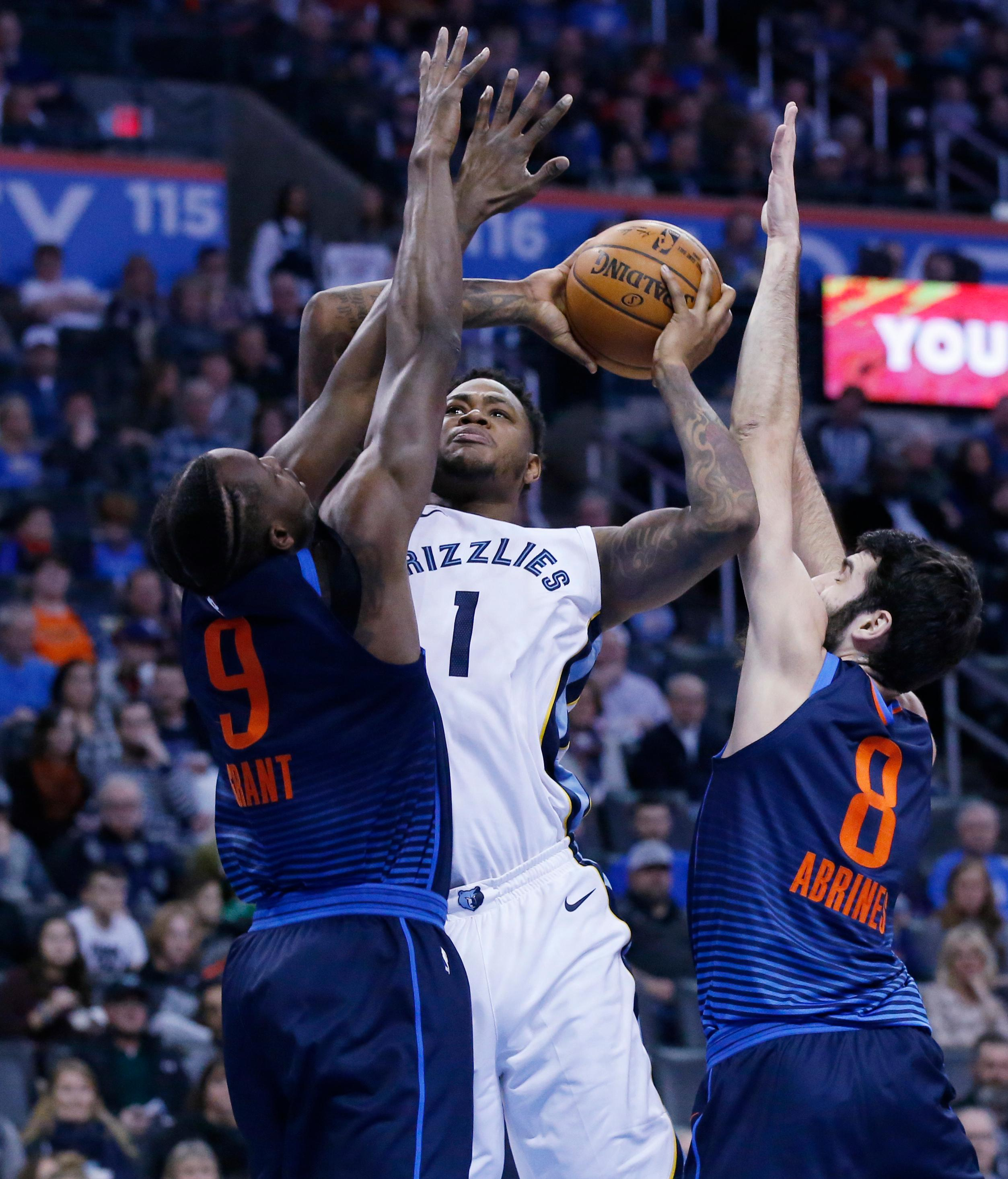 Memphis Grizzlies forward Jarell Martin (1) shoots between Oklahoma City Thunder forward Jerami Grant (9) and guard Alex Abrines (8) in the first half of an NBA basketball game in Oklahoma City, Sunday, Feb. 11, 2018. (AP Photo/Sue Ogrocki)