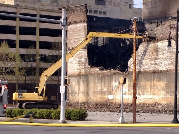 An excavator tears down a wall of the burned building in downtown Birmingham on Friday, March 29, 2013.