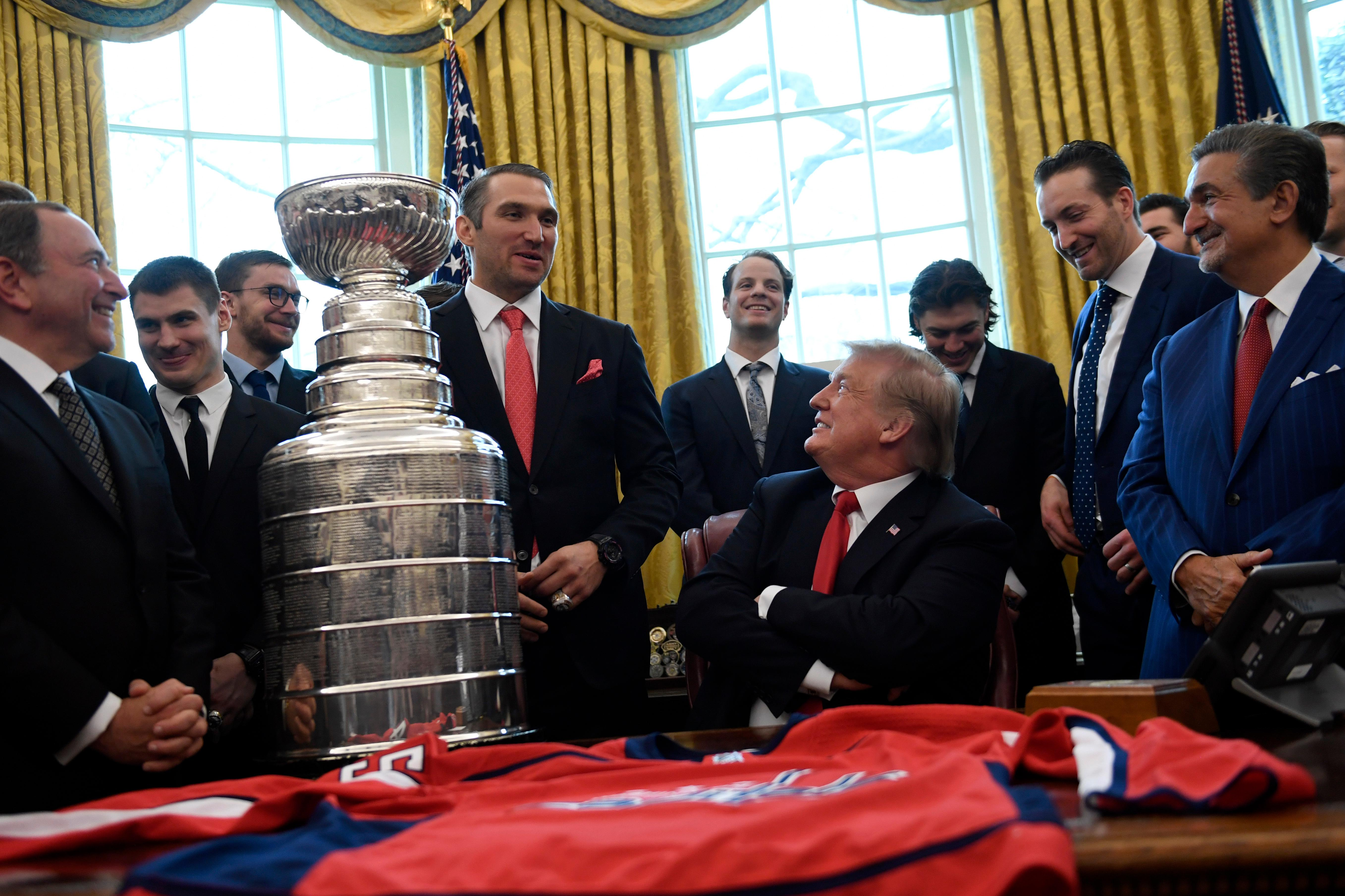 President Donald Trump, seated center, listens as Washington Capitals Alex Ovechkin, fourth from left, speaks during the teams visit to the Oval Office of the White House in Washington, Monday, March 25, 2019, to honor the 2018 Stanley Cup Champion Washington Capitals hockey team. Capitals owner Ted Leonsis, right, and NHL Commissioner Gery Bettman, left, and other members of the team listen. (AP Photo/Susan Walsh)
