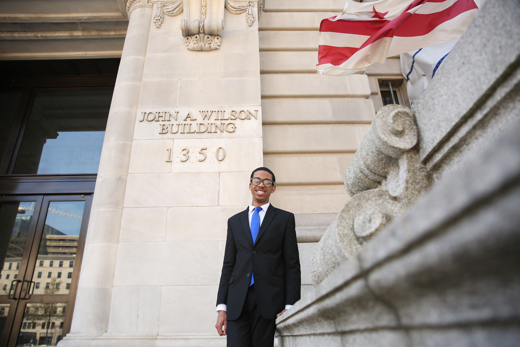 Michael Christian Woods poses in front of the Office of the Mayor. (Amanda Andrade-Rhoades/DC Refined)