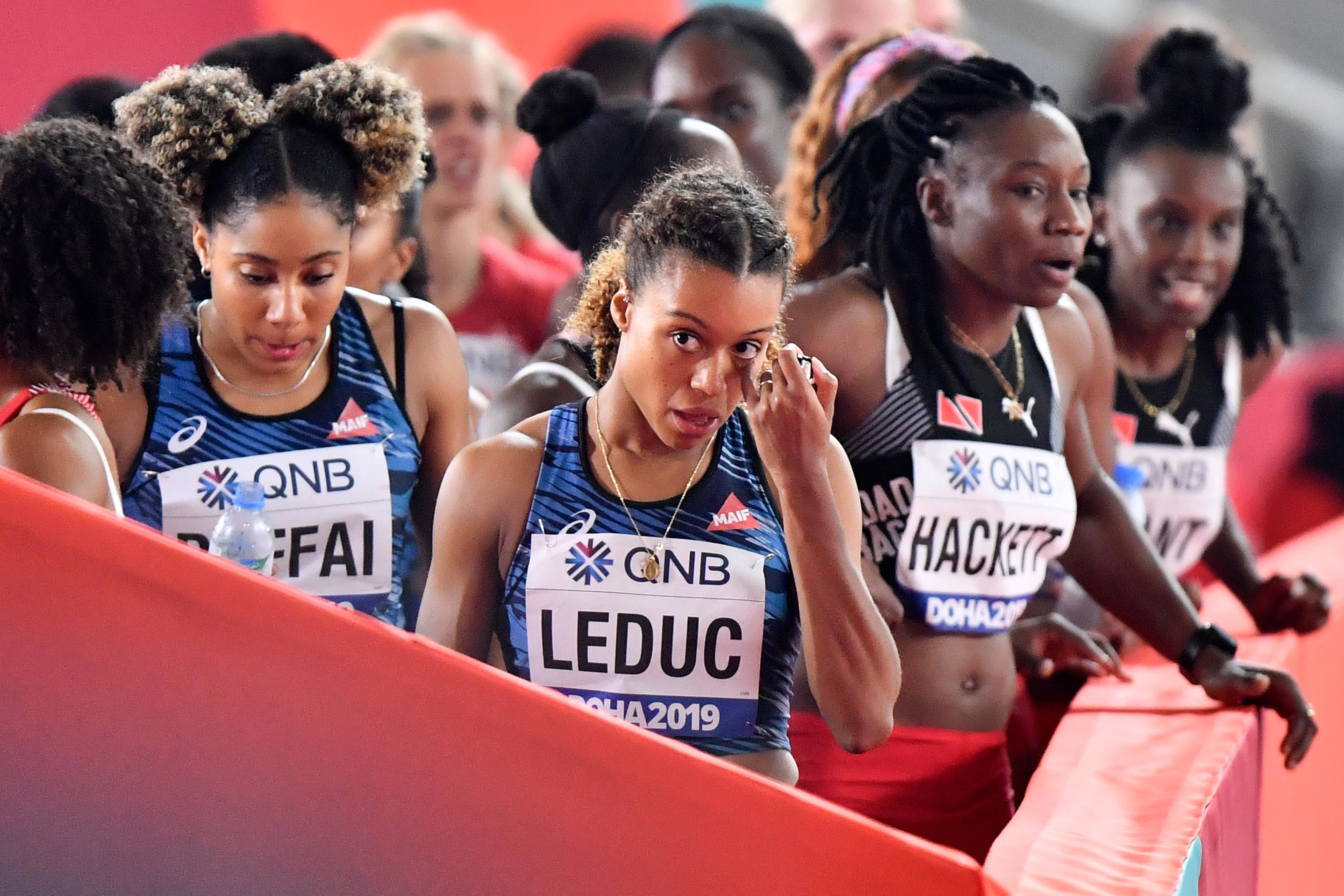 France's Cynthia Leduc, center, and Estelle Raffai, left, leave after their disqualification in the women's 4x100 meter relay at the World Athletics Championships in Doha, Qatar, Friday, Oct. 4, 2019. (AP Photo/Martin Meissner)
