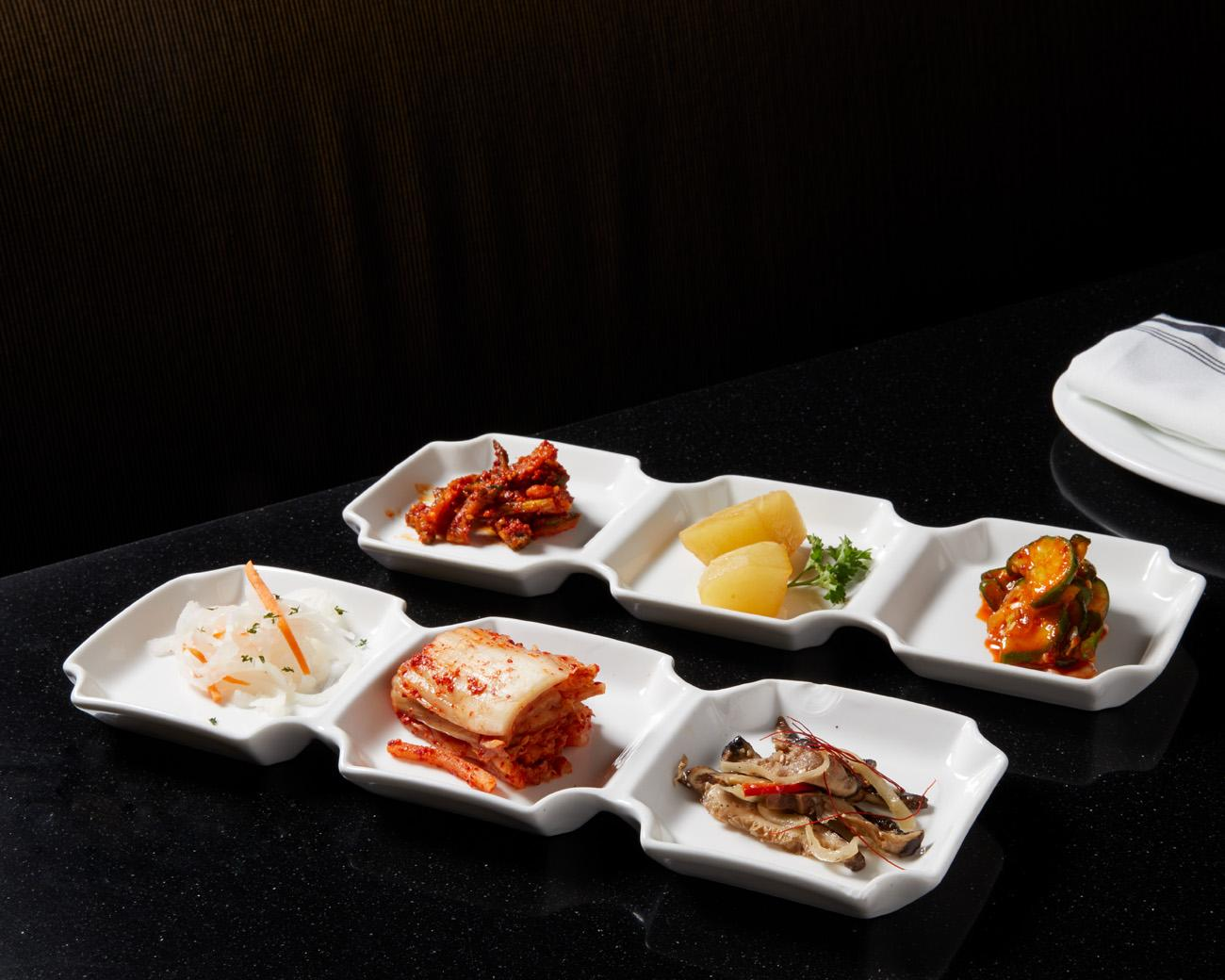 Banchan (a collection of small dishes) and assorted kimchi: pickled daikon, traditional kimchi, spicy daikon, roasted potato, shiitake mushroom salad, and cucumber spicy salad / Image: Marlene Rounds // Published 9.18.18