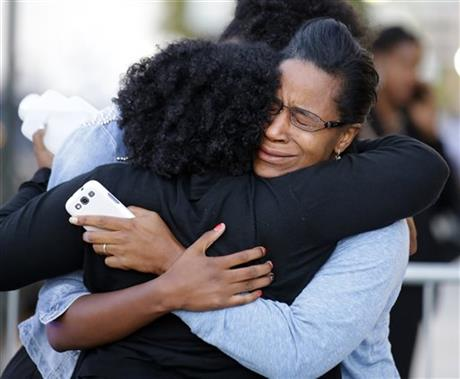 Three women embrace near Nationals Park where family members waited to greet loved ones that were at the Washington Navy Yard, Monday Sept. 16.