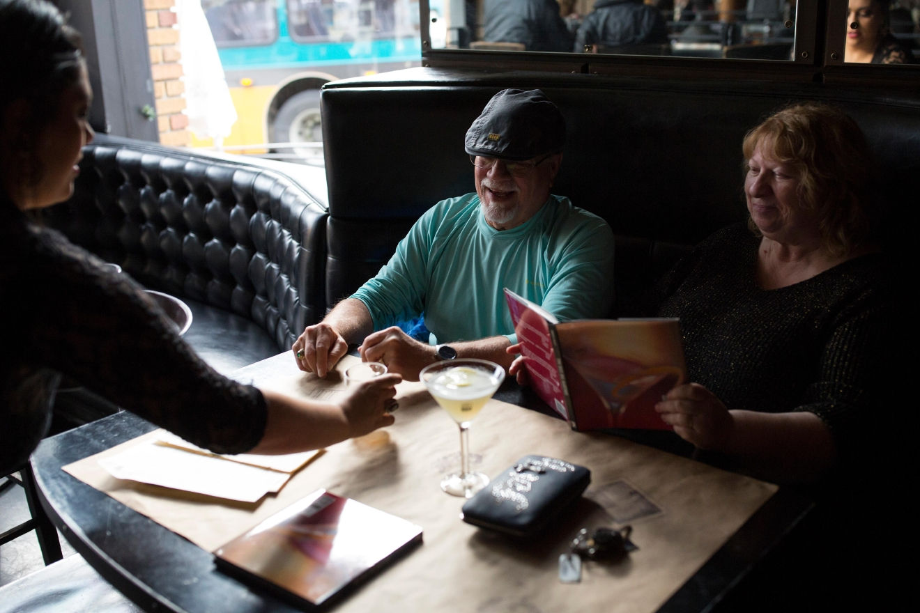 Seattle residents Bob and Carol Goodman are served up some of their last drinks during their first and last visit to Tini Bigs Lounge as the bar closes its doors after 20 years. (Sy Bean / Seattle Refined)