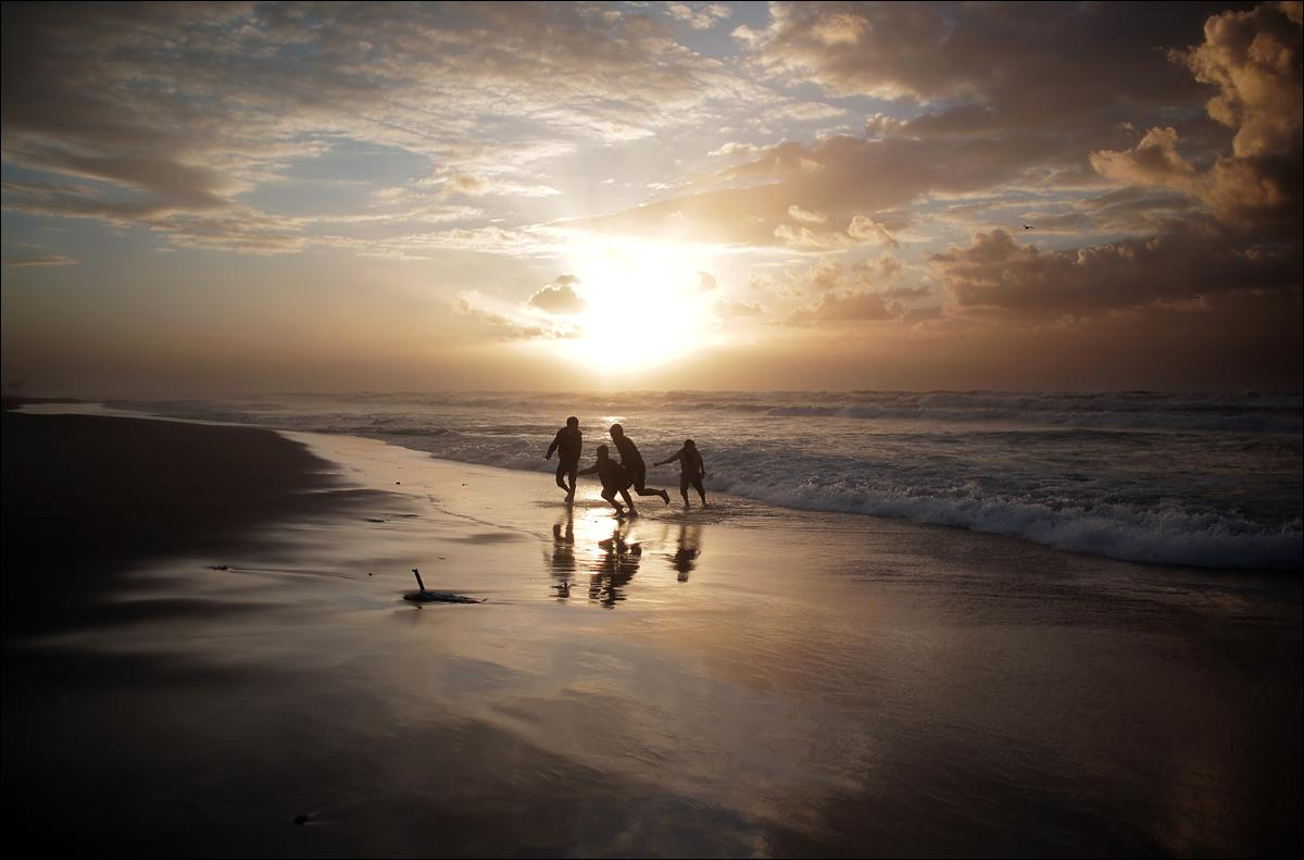 Palestinian children play on the beach as the sun sets in Gaza City, Tuesday, Jan. 19, 2016. (AP Photo/ Khalil Hamra)