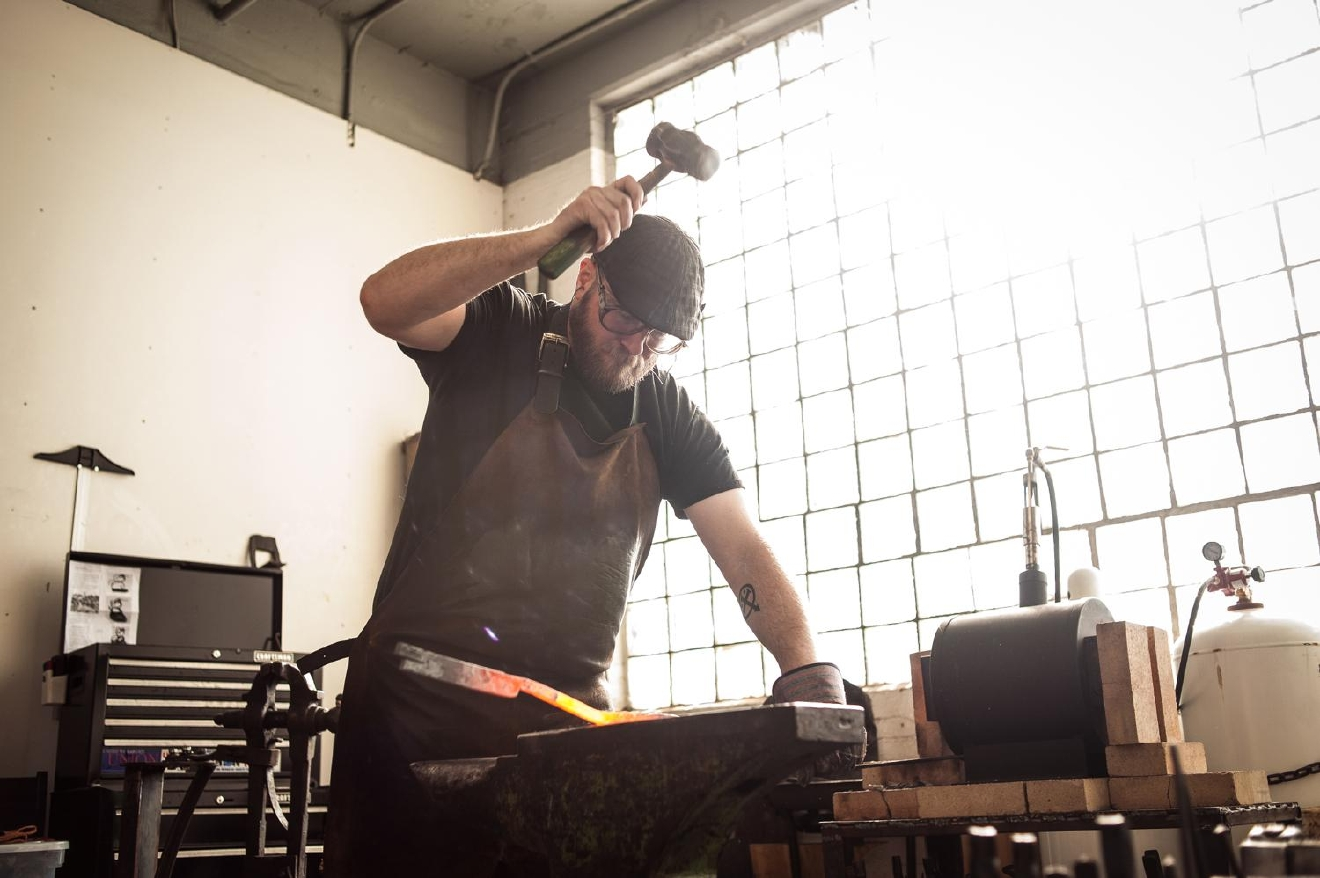 Mark Gilsdorf, Artist-Blacksmith, hammers a steel bar in his studio in Walnut Hills' Essex Studios. The main hammer he uses is a 4 lb. rounding hammer, which he forged himself in Mississippi while learning to become a blacksmith. / Image: Melissa Doss Sliney