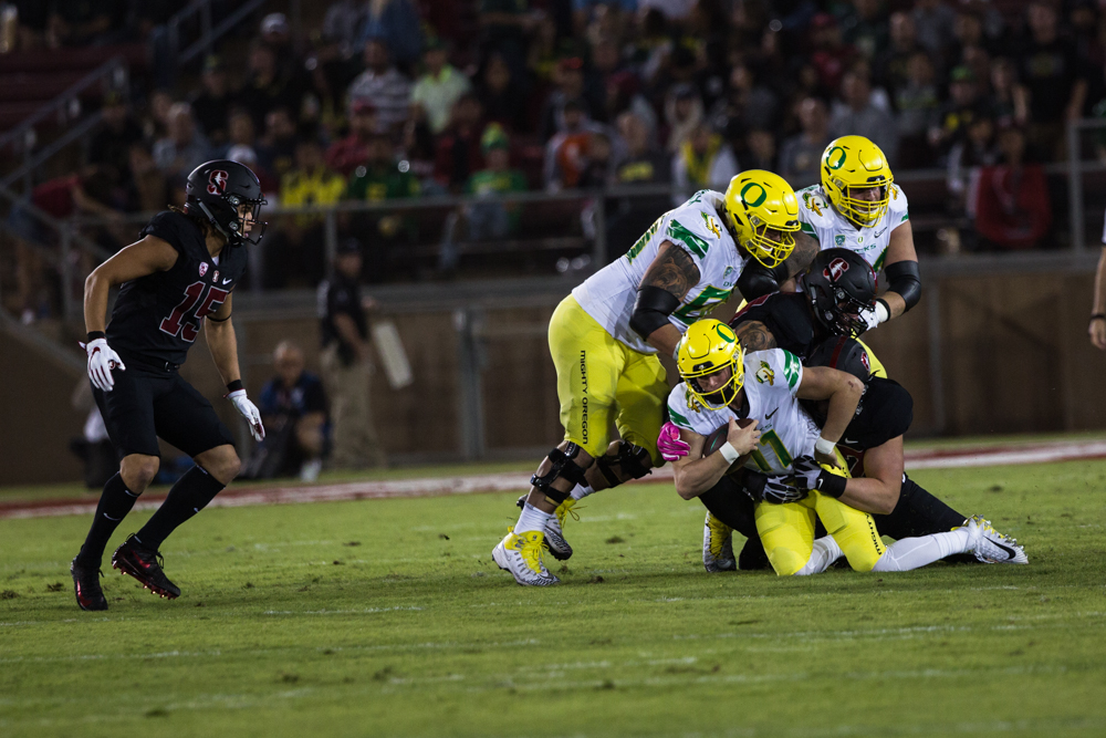 Oregon quarterback Braxton Burmeister (#11) is dragged down by to Stanford defenders. The Oregon Ducks are trailing the Stanford Cardinal 28-7 at halftime at Stanford Stadium in California.  Photo by Austin Hicks, Oregon News Lab