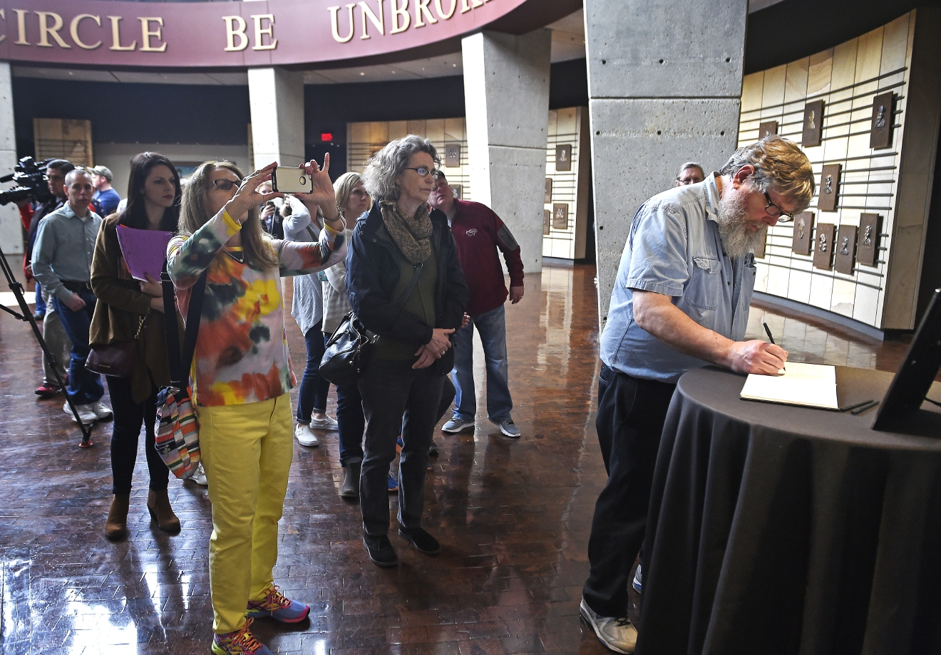 "Robert Grant signs his condolences along with other fans as they visit the plaque of Merle Haggard in the Rotunda Hall at the Country Music Hall of Fame, Wednesday April 6, 2016, in Nashville, Tenn., after learning of his death. Haggard, who rose from poverty and prison to international fame through his songs about outlaws, underdogs and an abiding sense of national pride in such hits as ""Okie From Muskogee"" and ""Sing Me Back Home,"" died Wednesday at 79, on his birthday. (Larry McCormack/The Tennessean via AP) NO SALES; MANDATORY CREDIT"