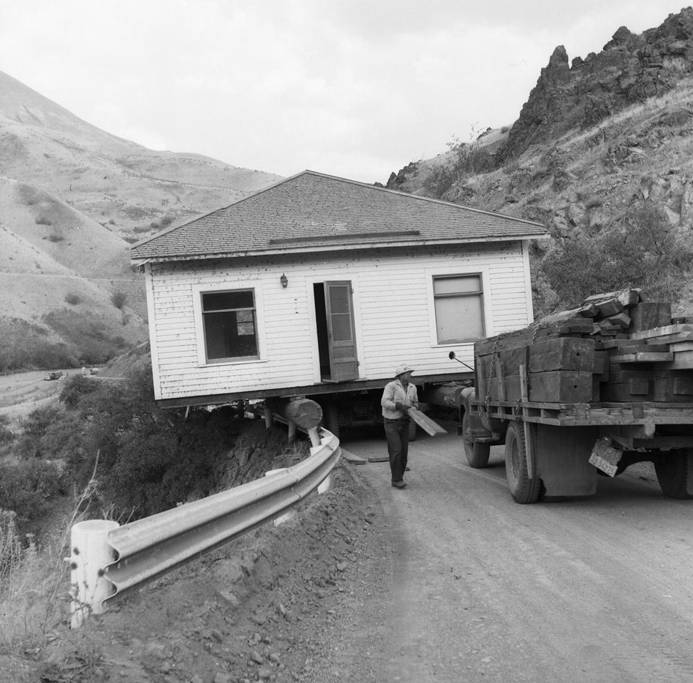 Moving Pete Basche's house from Robinette to Richland in 1957. The house, where Pete's daughter, Betty, lives today, is going down the grade to meet the Powder River, which is at the far left. (Pete Basche/Baker County Historic Photo Collection)