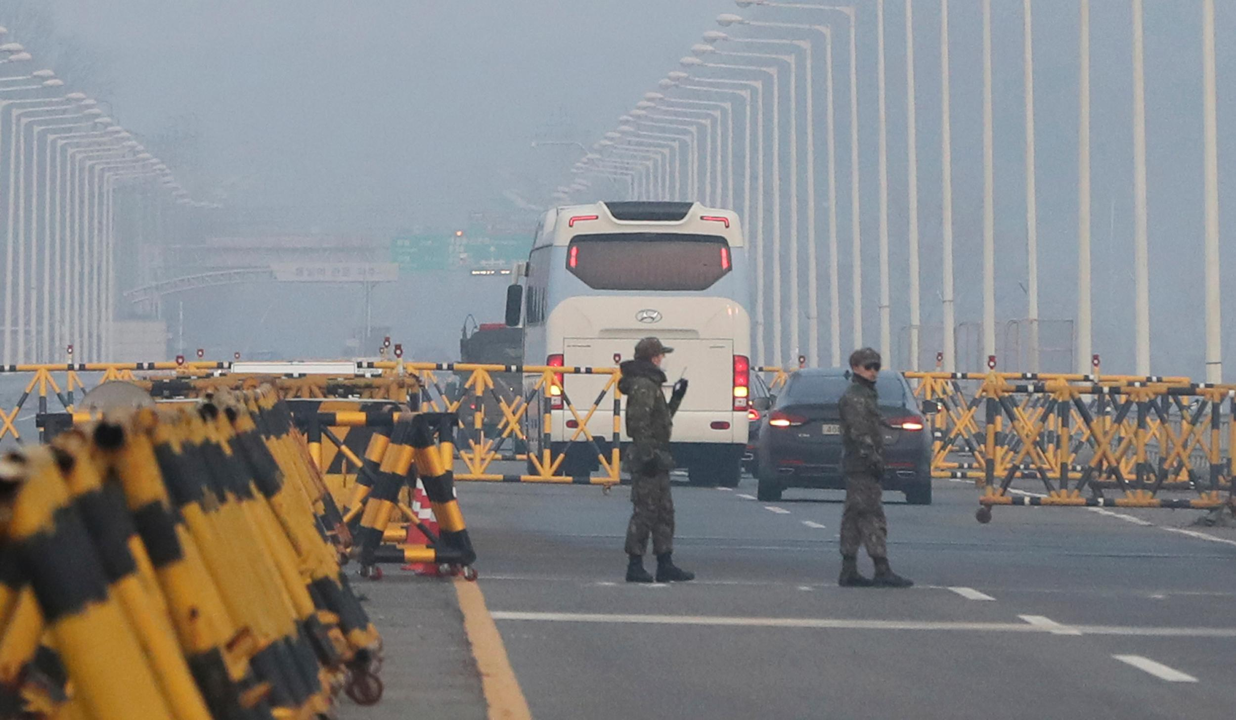 South Korean soldiers stand as vehicles carrying the South Korean delegation pass at Unification Bridge, which leads to the Panmunjom in the Demilitarized Zone in Paju, South Korea, Wednesday, Jan. 17, 2018. South Korean delegation departed for Panmunjom on Wednesday morning for talks with North Korea to further discuss the North's paricipation in the upcoming Winter Olympics. (AP Photo/Lee Jin-man)