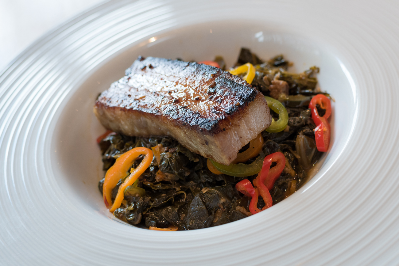 Collard greens with pork belly and pickled peppers. The pork is locally sourced from the Beller Family Homestead, a farm owned and operated by a police officer who's also a farmer. / Image: Phil Armstrong // Published: 9.9.17