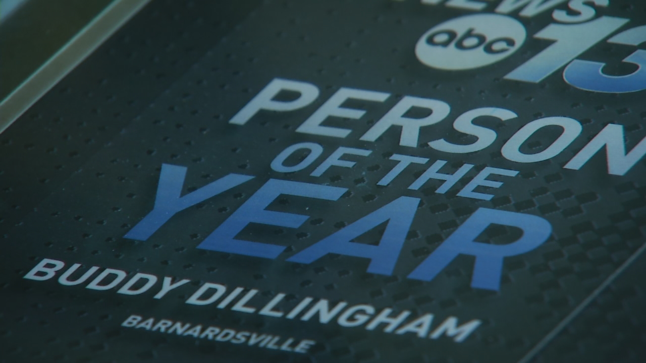 Reporter John Le presented Buddy Dillingham with a Person of the Year plaque as a group of friends gathered to shake his hand and tell him there's no one more deserving of such an honor. (Photo credit: WLOS Staff)