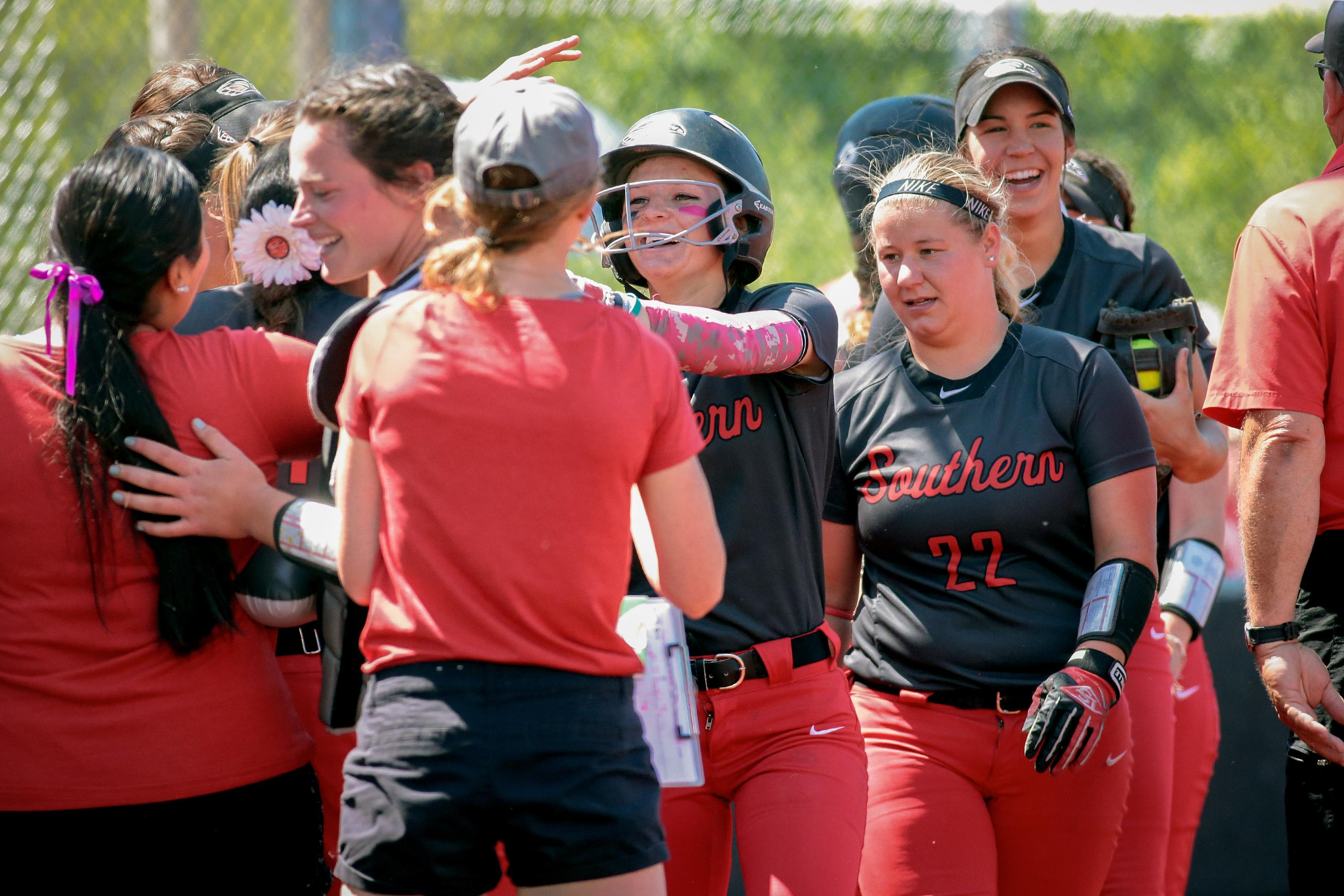 Southern Oregon University Kelsey Randall  (center) celebrates with teammates after hitting an In-The-Park Homerun against Simpson University at US Cellular Fields on Monday.[PHOTO BY:  LARRY STAUTH JR]