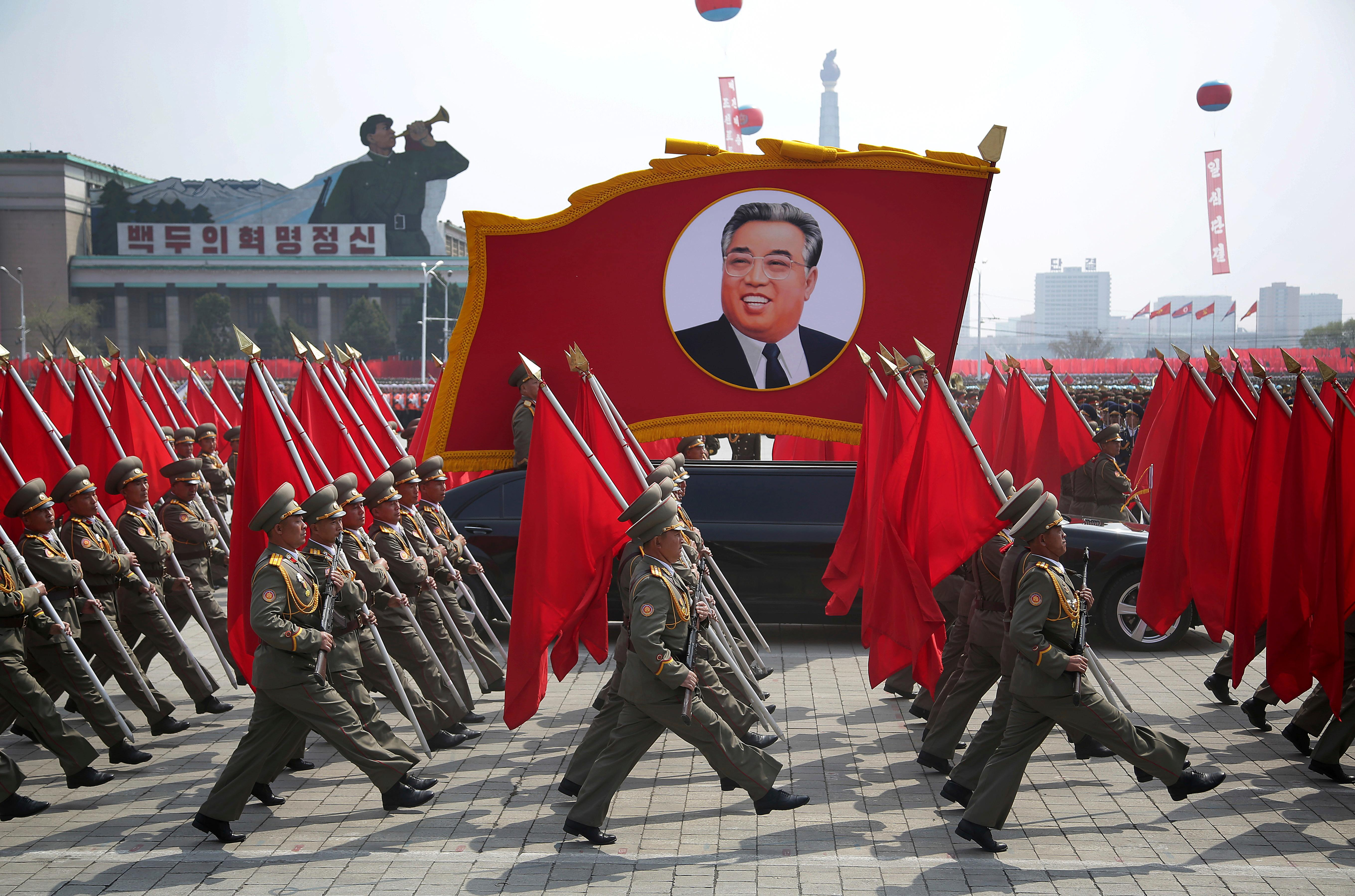 North Korean soldiers carry flags and a photo of late leader Kim Il Sung as they march across Kim Il Sung Square during a military parade on Saturday, April 15, 2017, in Pyongyang, North Korea to celebrate the 105th birth anniversary of Kim Il Sung, the country's late founder and grandfather of current ruler Kim Jong Un. (AP Photo/Wong Maye-E)