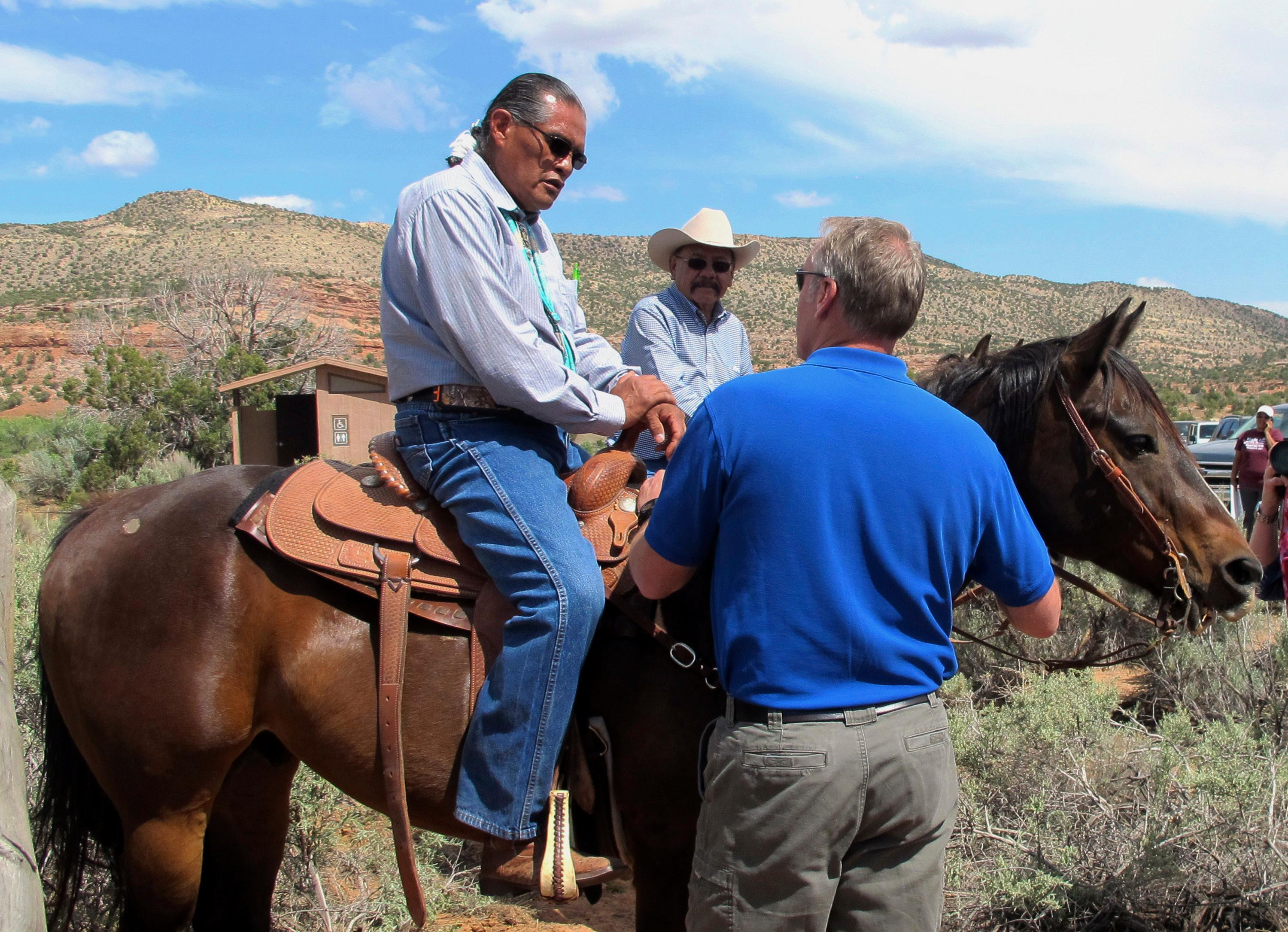 Interior Secretary Ryan Zinke, right, talks with two men on horses Monday, May 8, 2017, at the Butler Wash trailhead within Bears Ears National Monument near Blanding, Utah. Zinke says he wants to make sure Native American cultural standing is preserved in a new national monument but cautioned that not all tribal members share the same opinion about it. (AP Photo/Michelle Price)