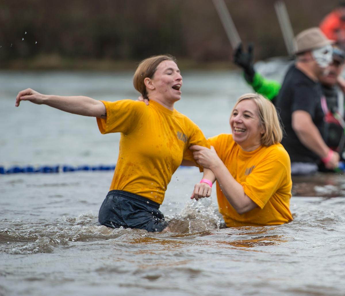 Two participants hold onto each other in the cold water. Plungers and onlookers gather for the annual Special Olympics Polar Plunge at Maurie Jacobs Park in Eugene. With over 250 plungers diving into the Willamette River, participants look to surpass $412,000, which was last years total. Eugene is just one of the five locations around Oregon that hosts the plunge, but is a nationwide event. The funds raised by today�s plunge will go towards assisting Oregon Special Olympic teams. Photo by Savannah Blake, Oregon News Lab