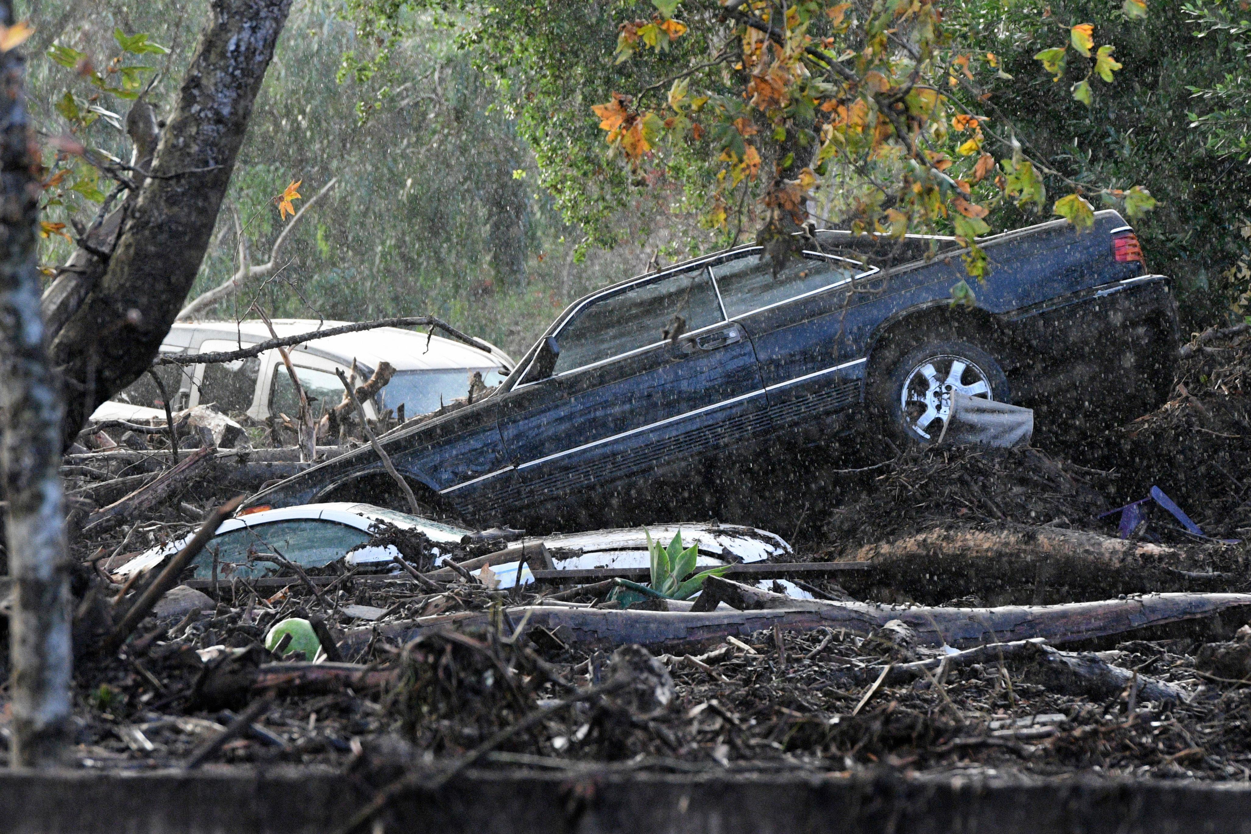 Cars that were washed away are piled up on the banks of Romero Creek in Montecito, Calif., Tuesday, Jan. 9, 2018. Dozens of homes were swept away or heavily damaged Tuesday as downpours sent mud and boulders roaring down hills stripped of vegetation by a gigantic wildfire that raged in Southern California last month. (AP Photo/Michael Owen Baker)
