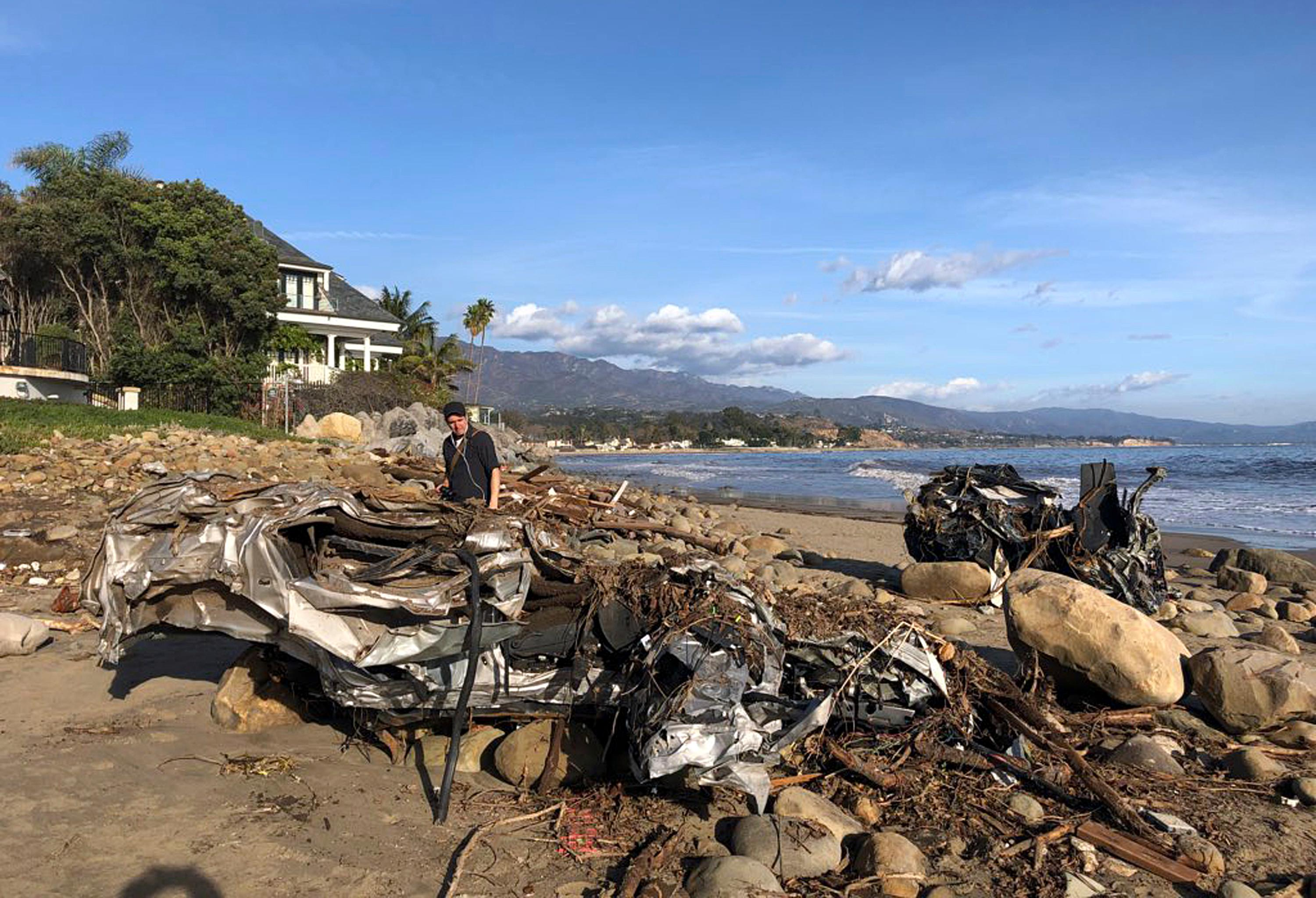This photo provided by the Santa Barbara County Fire Department shows the wreckage of two autos on the beach that were carried by floodwaters down Montecito Creek Tuesday all the way to the Pacific Ocean in Montecito, Calif., Wednesday, Jan. 10, 2018. Anxious family members awaited word on loved ones Wednesday as rescue crews searched grimy debris and ruins for more than a dozen people missing after mudslides in Southern California destroyed houses, swept cars to the beach and left more than a dozen victims dead. (Mike Eliason/Santa Barbara County Fire Department via AP)