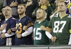 Fans lock arms during the national anthem before a game between the Green Bay Packers and the Chicago Bears Thursday, Sept. 28, 2017, in Green Bay.