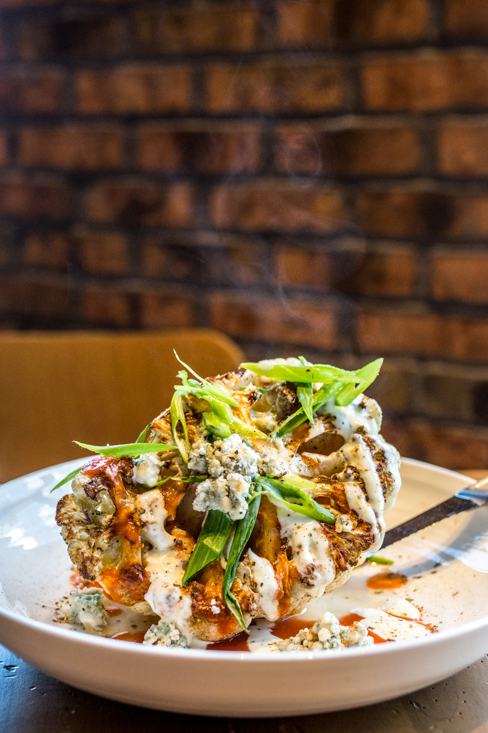 Buffalo Cauliflower: cast iron-seared, al dente roasted cauliflower with a tangy hot sauce, smoked ranch, Danish blue cheese crumbles, and garnished with green onions and house seasonings / Image: Catherine Viox{ }// Published: 10.10.19