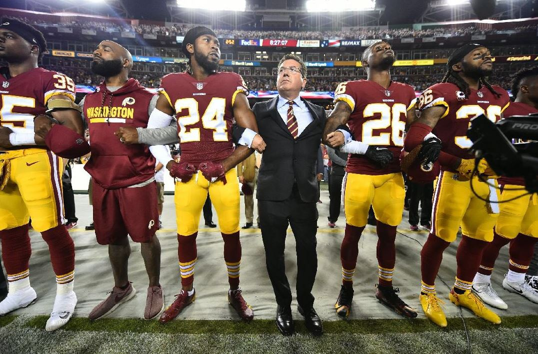 Redskins Owner Daniel Snyder links arms with players during the National Anthem on Sunday, September 24, 2017, against the Oakland Raiders in Landover, Maryland. (Photo Property of the Washington Redskins)