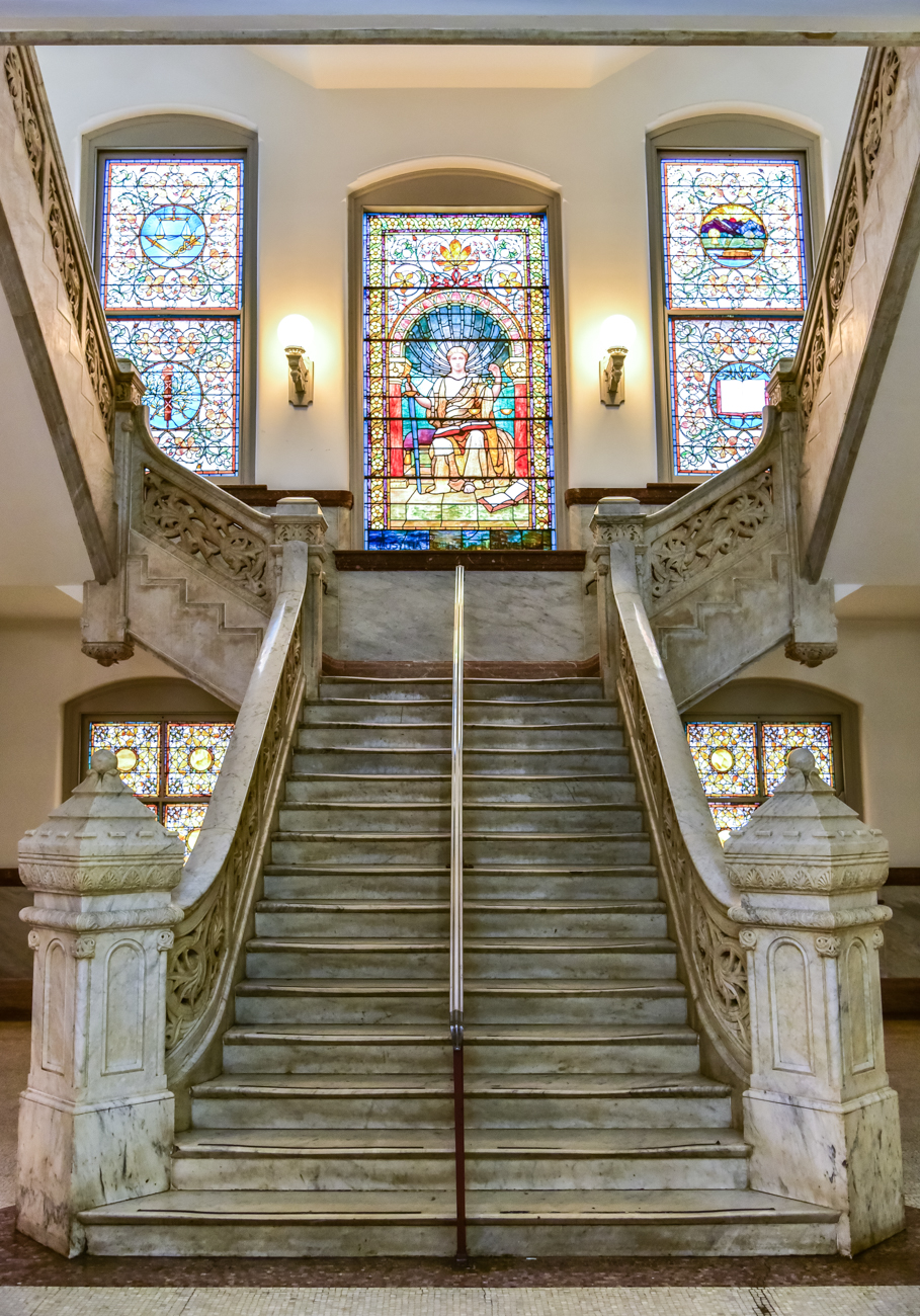 Incredible marble staircases outfitted with colorful stained glass windows can be found on every accessible floor at the Plum Street side of the building. The stained glass windows tell the tale of Cincinnati's history through imagery. / Image: Phil Armstrong, Cincinnati Refined // Published: 1.20.17