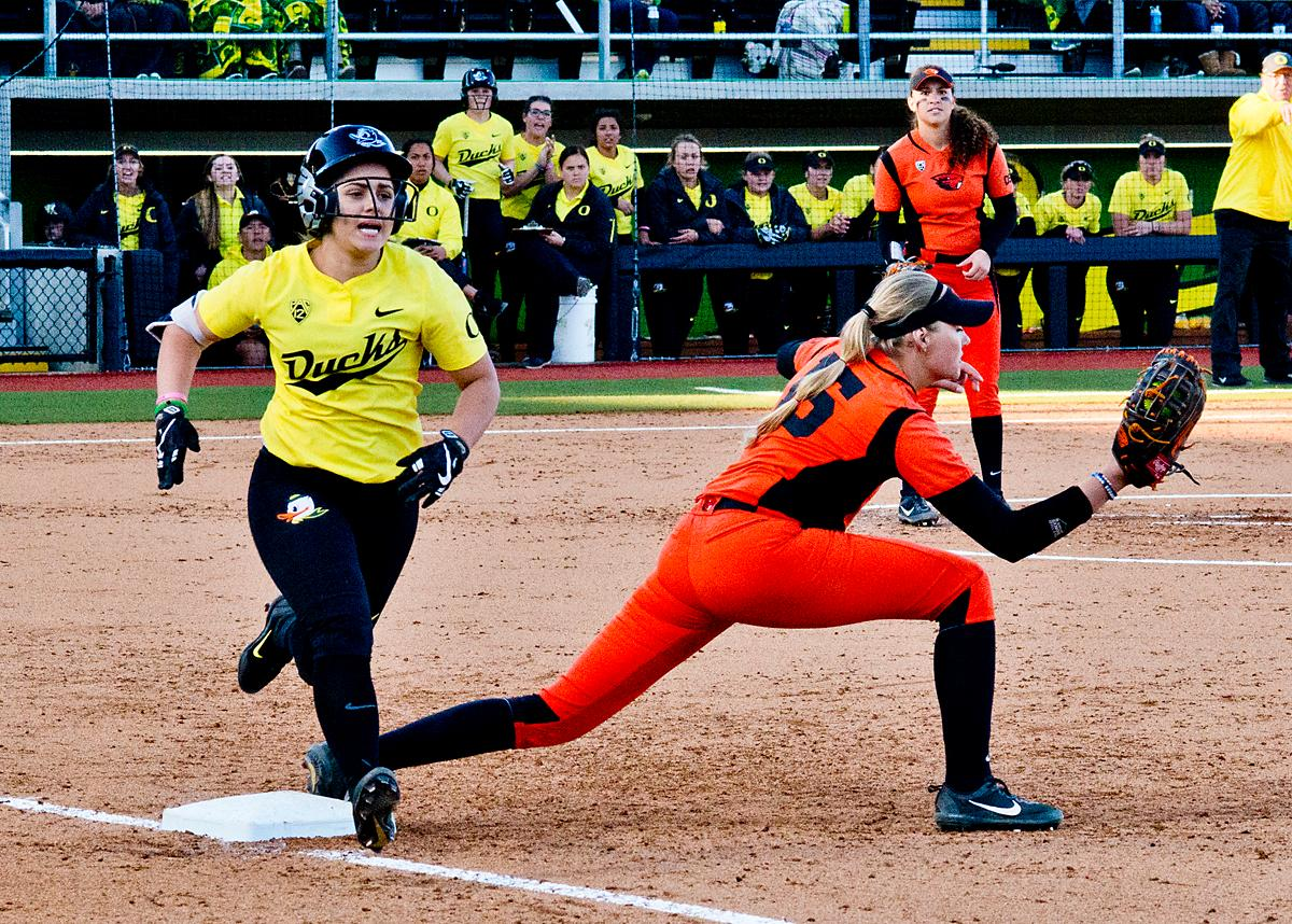 Oregon Ducks Mia Camuso (#7) beats the throw to Oregon State Beavers first base player Natalie Hampton (#15). The Oregon Ducks defeated the Oregon State Beavers 8-0 in game one of the three-game Civil War series on Friday night at Jane Sanders Stadium. The game was 0-0 until Gwen Svekis (#21) hit a solo homerun in the fourth inning. Mia Camuso hit a grand slam in the fifth inning, ending the game for the Ducks by mercy rule. Photo by Dan Morrison