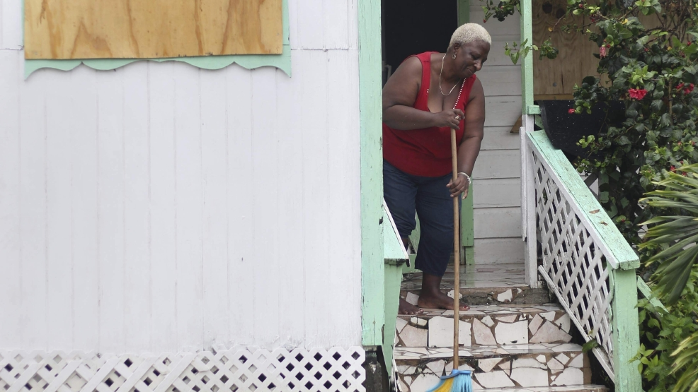 A woman pushes out floodwaters on her property after the passing of Hurricane Irma, in St. John's, Antigua and Barbuda, Wednesday, Sept. 6, 2017. Heavy rain and 185-mph winds lashed the Virgin Islands and Puerto Rico's northeast coast as Irma, the strongest Atlantic Ocean hurricane ever measured, roared through Caribbean islands on its way to a possible hit on South Florida. (AP Photo/Johnny Jno-Baptiste)