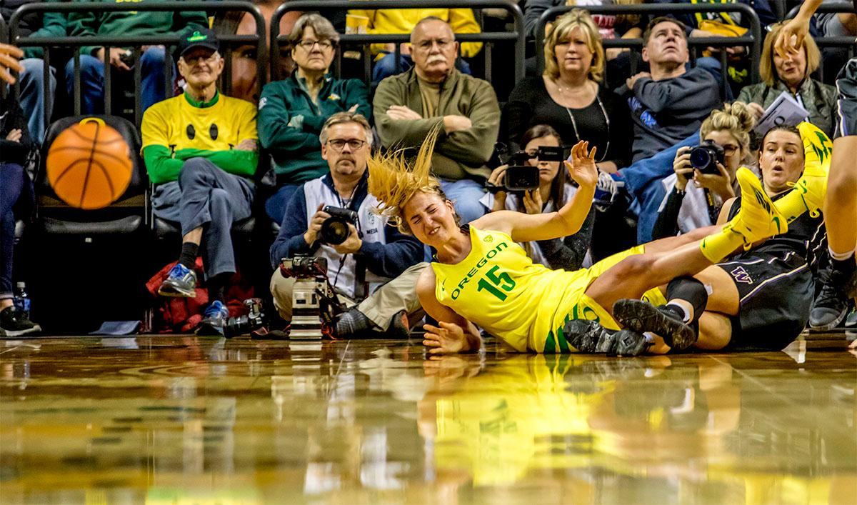 The Duck's Anneli Maley (#15) takes a tumble over the Huskies' Missy Peterson (#44). The Oregon Ducks defeated the Washington Huskies 94-83 on Sunday at Matthew Knight Arena. The victory was Head Coach Kelly Graves' 500th career win. Sabrina Ionescu also set the new NCAA all time record of 8 triple doubles in just 48 games. The previous record was 7 triple doubles in 124 games, held by Susie McConnell at Penn State. The Ducks will next face off against USC on Friday January 5th in Los Angeles. Photo by Rhianna Gelhart, Oregon News Lab
