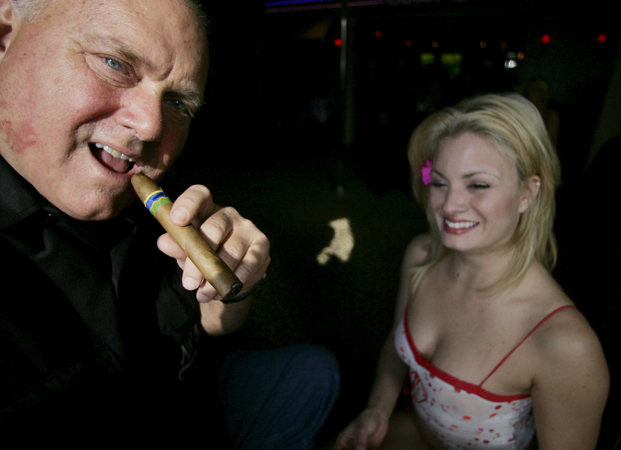 Moonlite BunnyRanch owner Dennis Hof smokes a cigar at his brothel's entrance, Thursday, April 7, 2005, in Mound House, Nev. (AP Photo/Brad Horn)