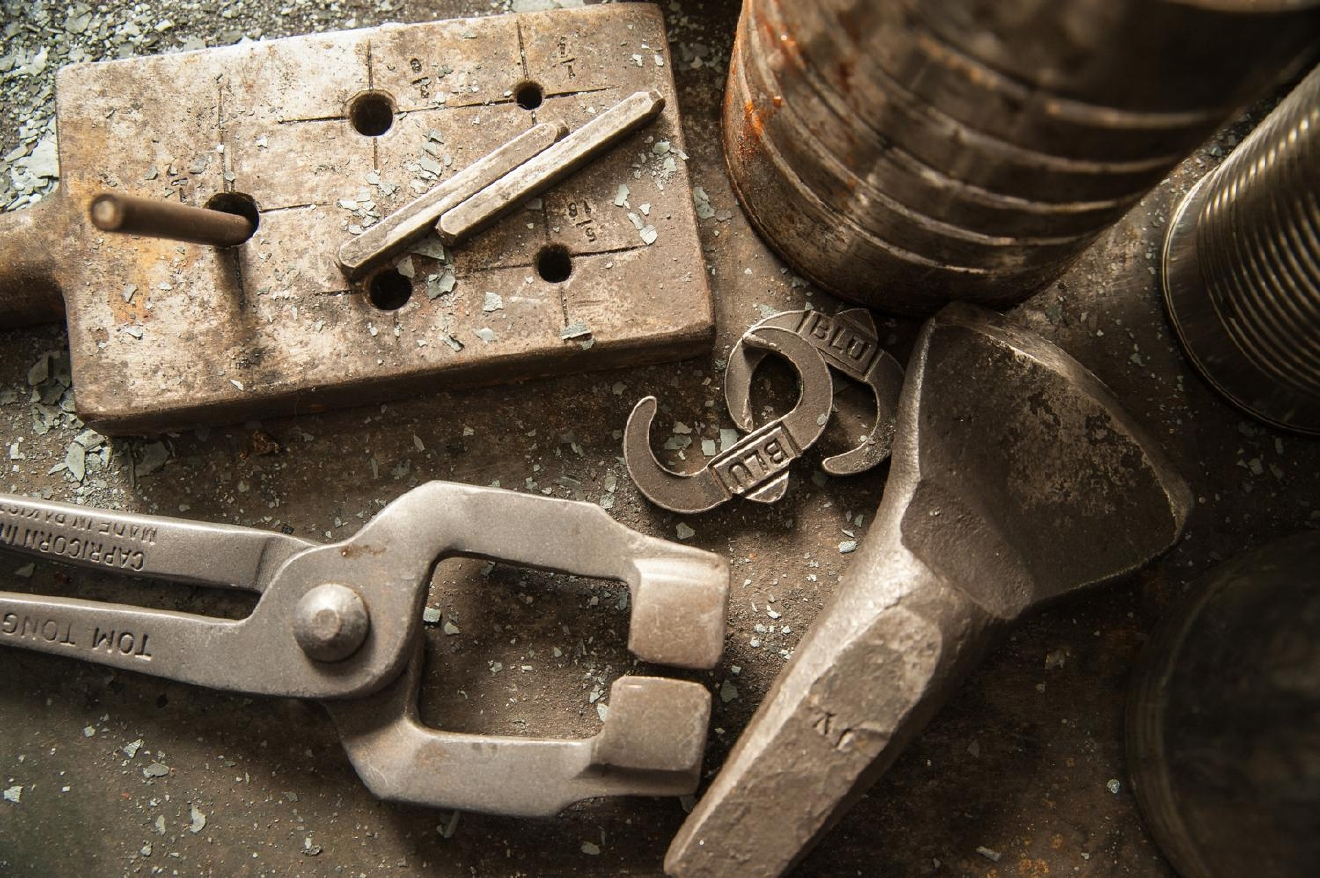 Various tools are pictured on a work table. Some of the pliers and tongs he uses were made with his main tool, a 4 lb. rounding hammer that he forged in the early days of learning the ropes as a blacksmith. / Image: Melissa Doss Sliney