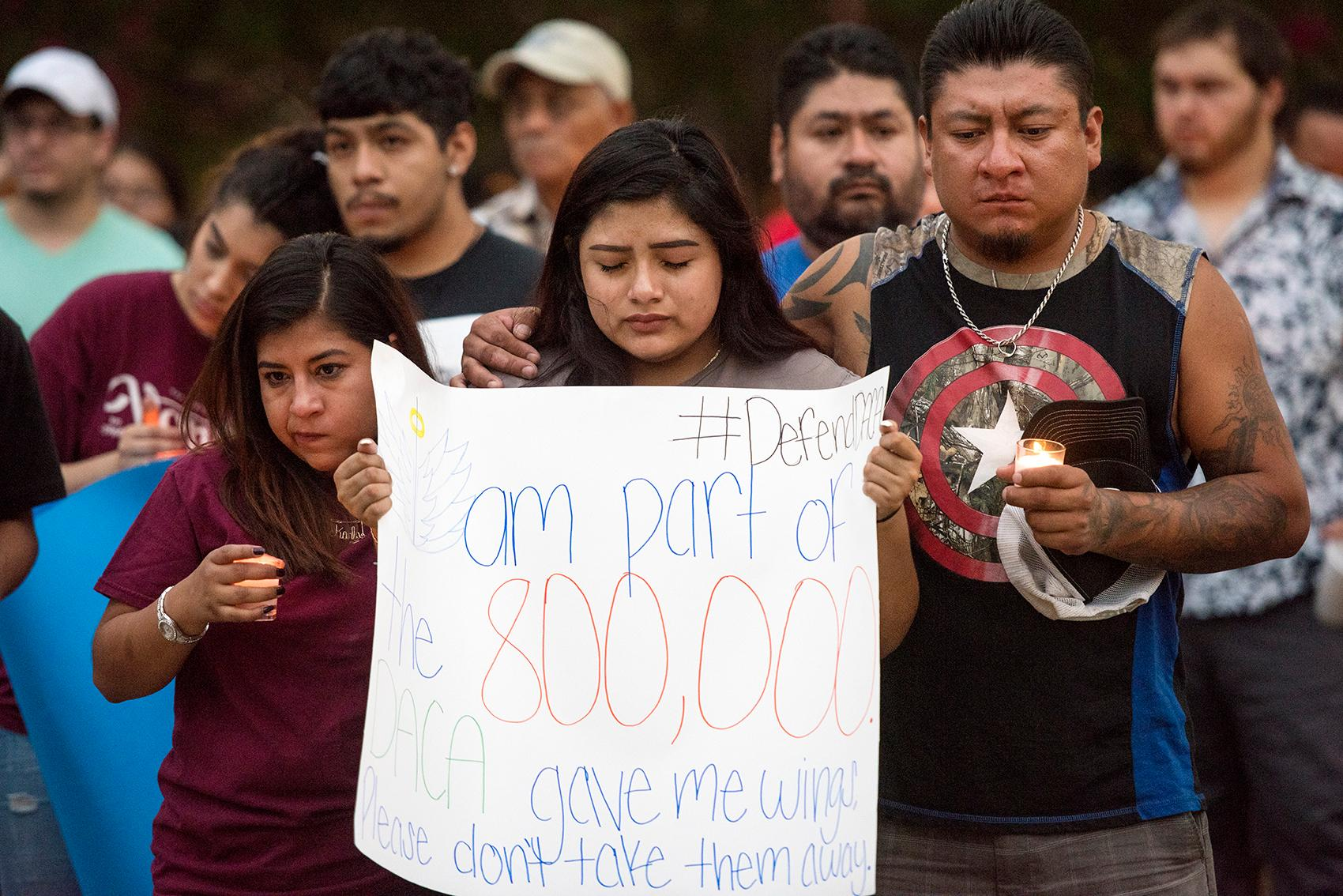 FILE - In this Sept. 5, 2017 file photo, Robert E. Lee student Karina Fraga, a DACA recipient, closes her eyes in prayer as she holds a sign during a silent vigil in honor of Deferred Action for Childhood Arrivals (DACA) at T.B. Butler Fountain Plaza in Tyler, Texas. Young immigrants in Houston and Miami are scrambling to complete their renewal applications for a program shielding them from deportation while dealing with hurricanes that have hit or are bearing down on their states. An Oct. 5 deadline was announced this week by the Trump administration. It set off an immediate scramble among many of the nearly 800,000 people protected by the DACA program, most notably in Texas and Florida. (Chelsea Purgahn/Tyler Morning Telegraph via AP, File)