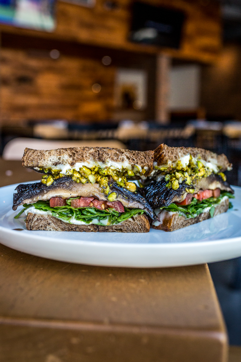 Portabella Melt: over roasted portabella mushroom on local grilled rye with arugula, Roma tomato slices, tangy goat cheese, parlor blend cheese, and pistachio pesto / Image: Catherine Viox // Published: 10.10.19