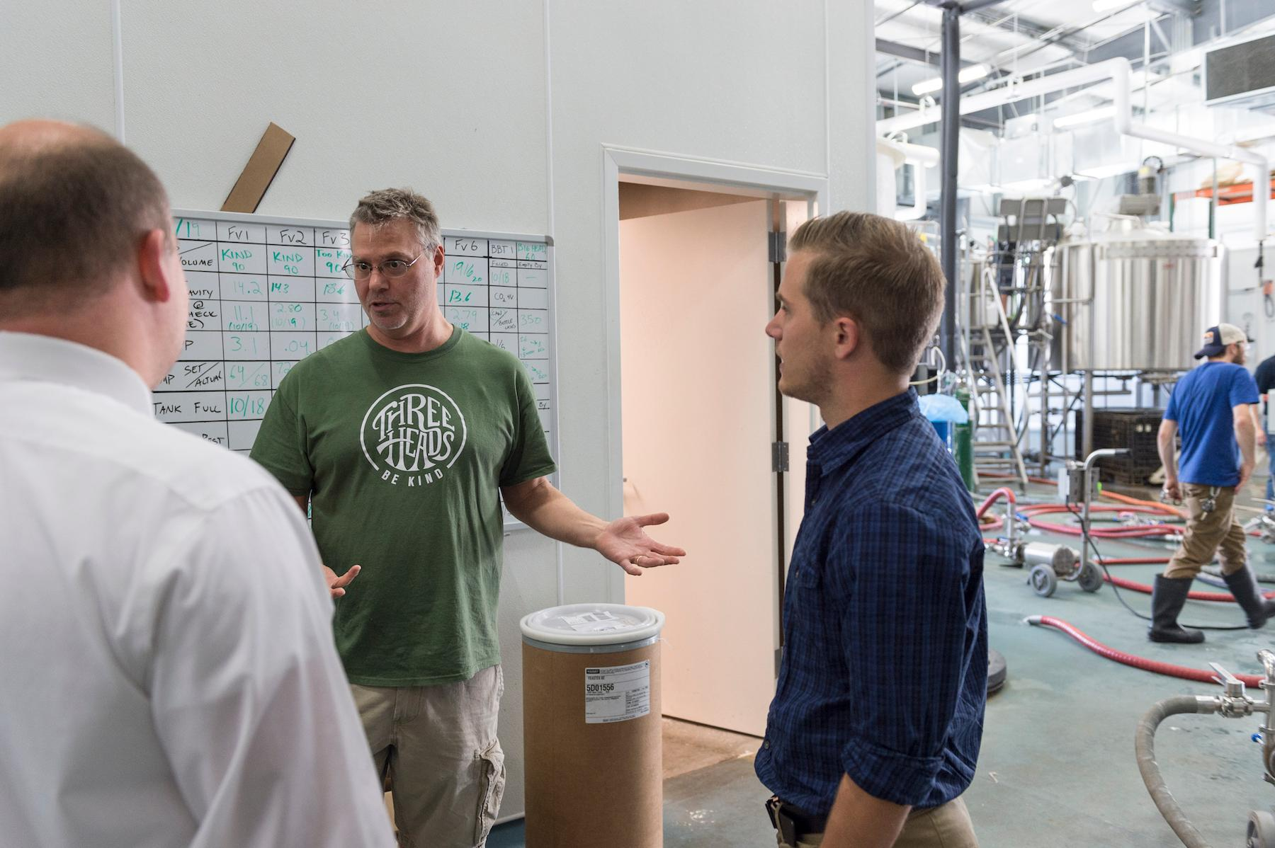 Three Heads Brewing President Dan Nothnagle, center, talks with Todd Raethka, left, operations manager of RIT Catering, and Eric Fox, supervisor for RIT Catering. Credit: Elizabeth Lamark