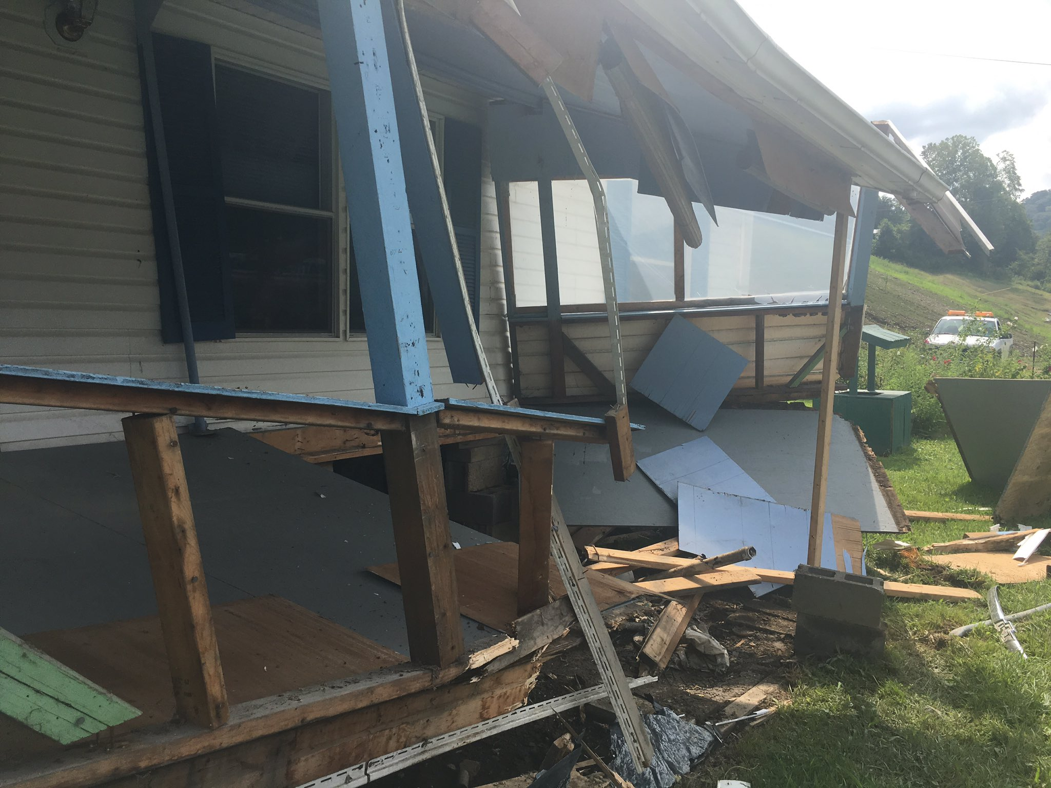 Neighbors say a pickup truck struck a utility pole and then the porch of a mobile home Friday in Boone County. (WCHS/WVAH)