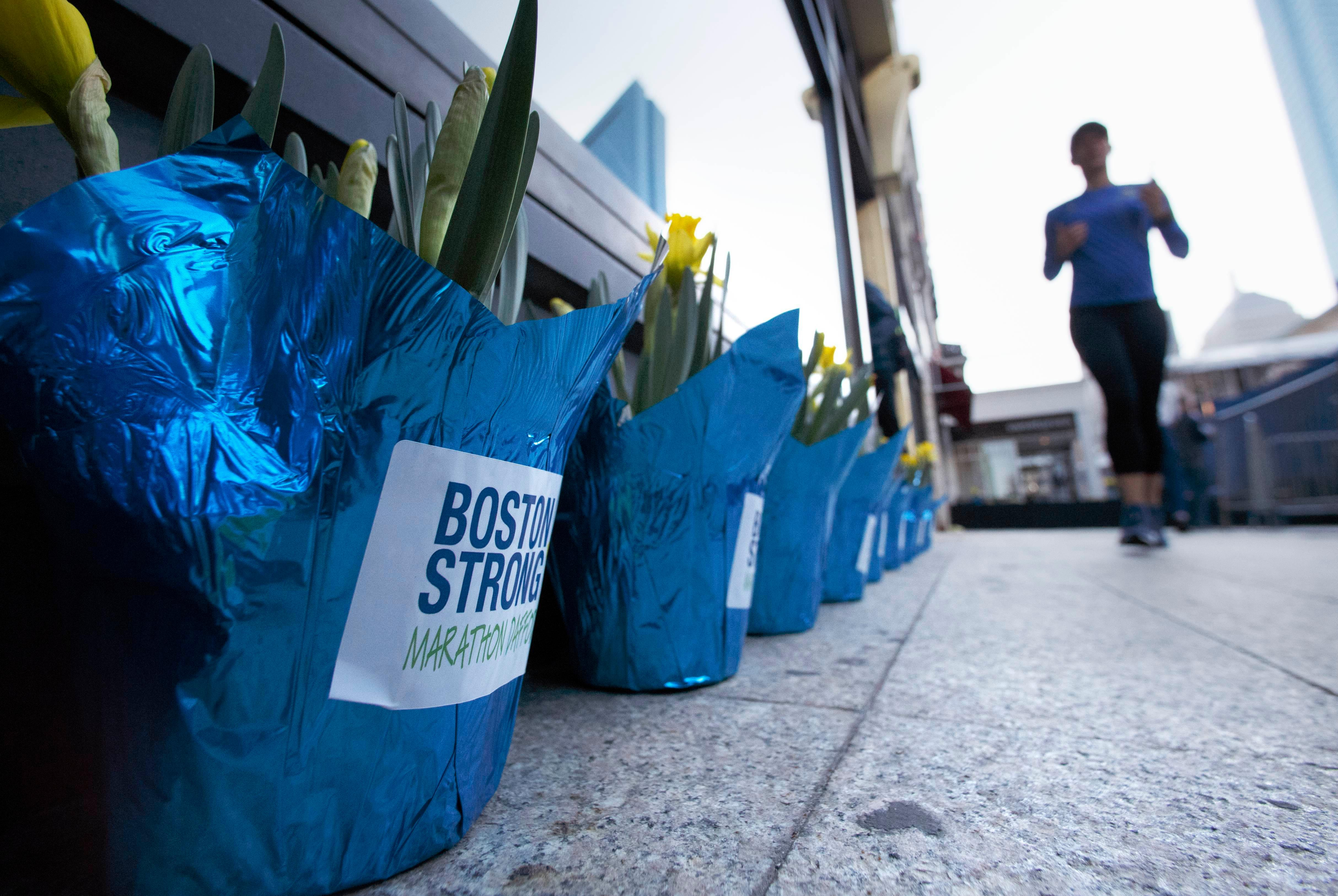 A runner passes flowers placed at the site of the bombing at the Boston Marathon finish line, Saturday, April 15, 2017, in Boston.  Bostonians are marking the fourth anniversary of the deadly 2013 Boston Marathon attacks. (AP Photo/Michael Dwyer)