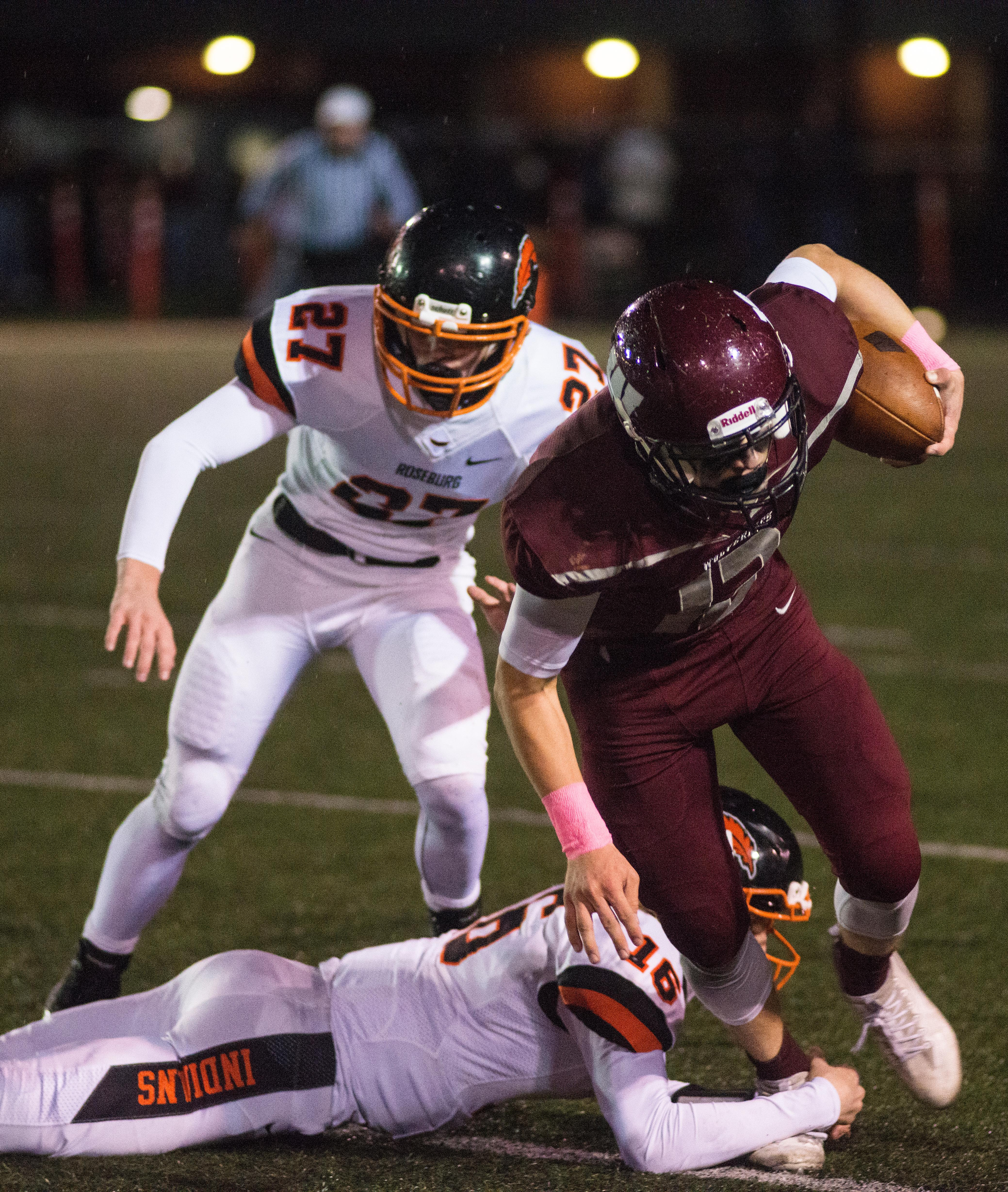 Willamette Wolverines Griffin LaVassaur (#12) attempts to carry the ball past Roseburg's defense. Roseburg Indians defeated Willamette Wolverines 21-20 at Wolverine Stadium on Friday night in Eugene. Photo by Rhianna Gelhart, Oregon News Lab