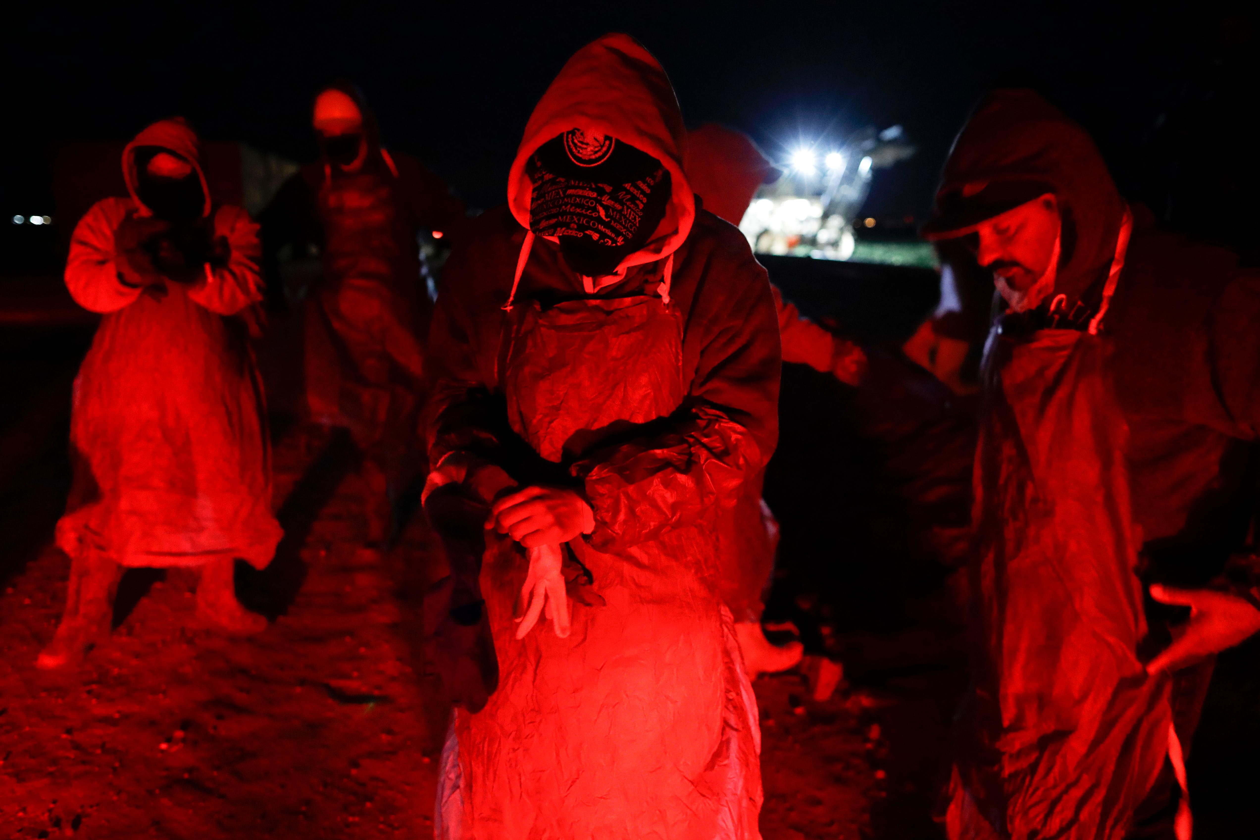 "In this March 6, 2018 photo, farmworker Eduardo Garcia, of Mexicali, Mexico, center, puts on an apron and gloves in the glow from the taillights of a bus, as he and his crew arrive at a cabbage field ready for harvest, before dawn outside of Calexico, Calif. For decades, cross-border commuters have picked lettuce, carrots, broccoli, onions, cauliflower and other vegetables that make California's Imperial Valley ""America's Salad Bowl"" from December through March. As Trump visits the border for the first time as president on Tuesday, March 13, the harvest is a reminder of how little has changed despite heated rhetoric in Washington. (AP Photo/Gregory Bull)"