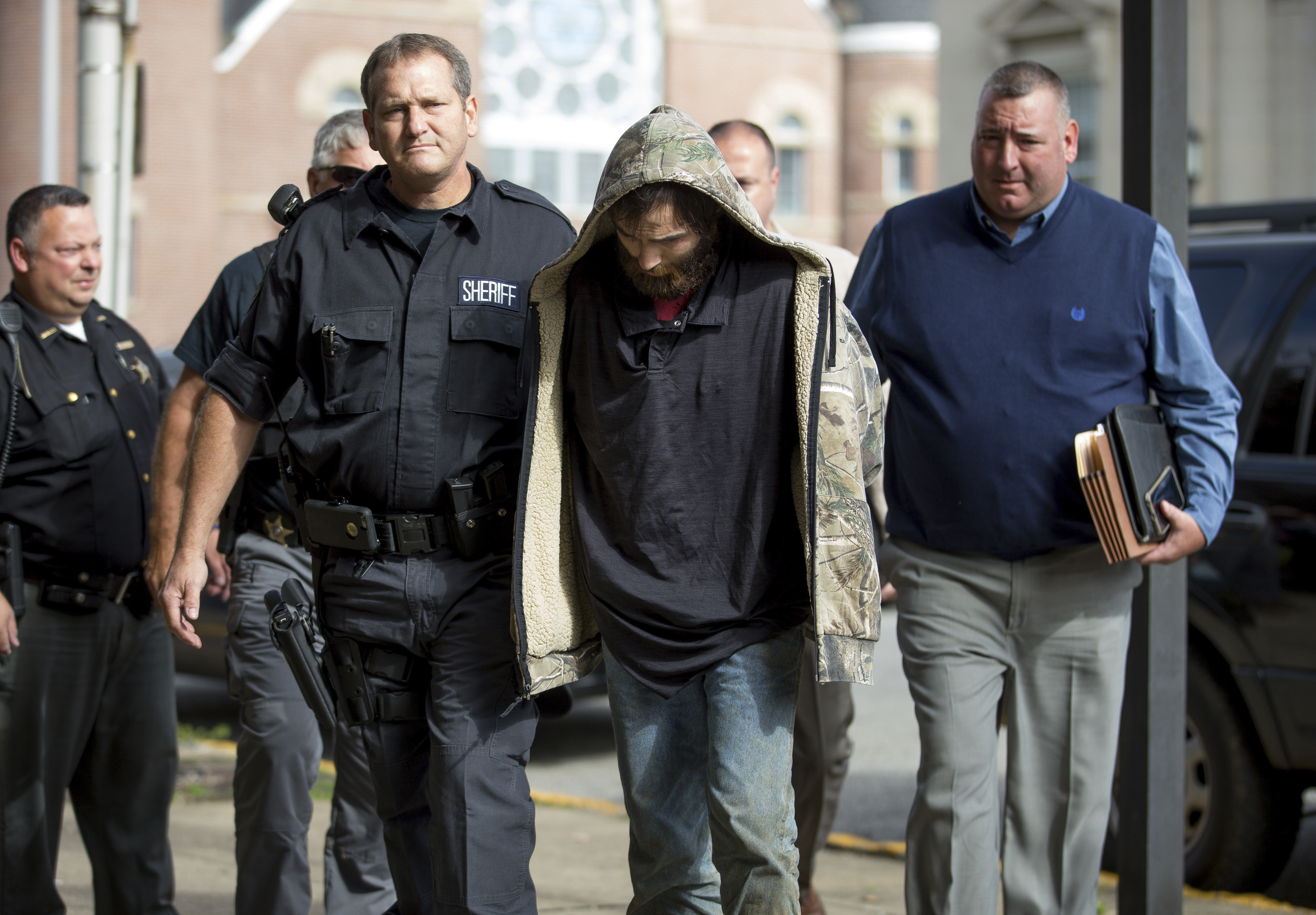 Lawrence County Sheriff Jeff Lawless escorts in Arron Lee Lawson after he was captured on Friday, Oct. 13, 2017, in Ironton, Ohio. Lawson has been arrested on three counts of murder and one count of aggravated murder.(Sholten Singer/The Herald-Dispatch via AP)