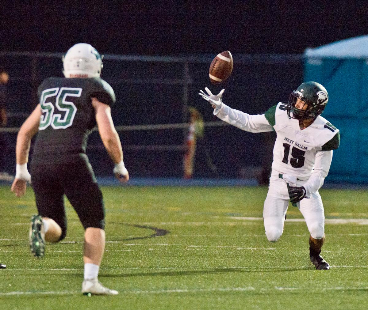West Salem Titans wide receiver Anthony Gould (#15) can't hold on to a long pass as Sheldon Irish linebacker Chris Collins (#55) closes in. On a rainy Monday evening Sheldon defeated West Salem 41-7. The game had been postponed from Friday due to unhealthy levels of smoke in the atmosphere due to nearby forest fires. Photo by Dan Morrison, Oregon News Lab