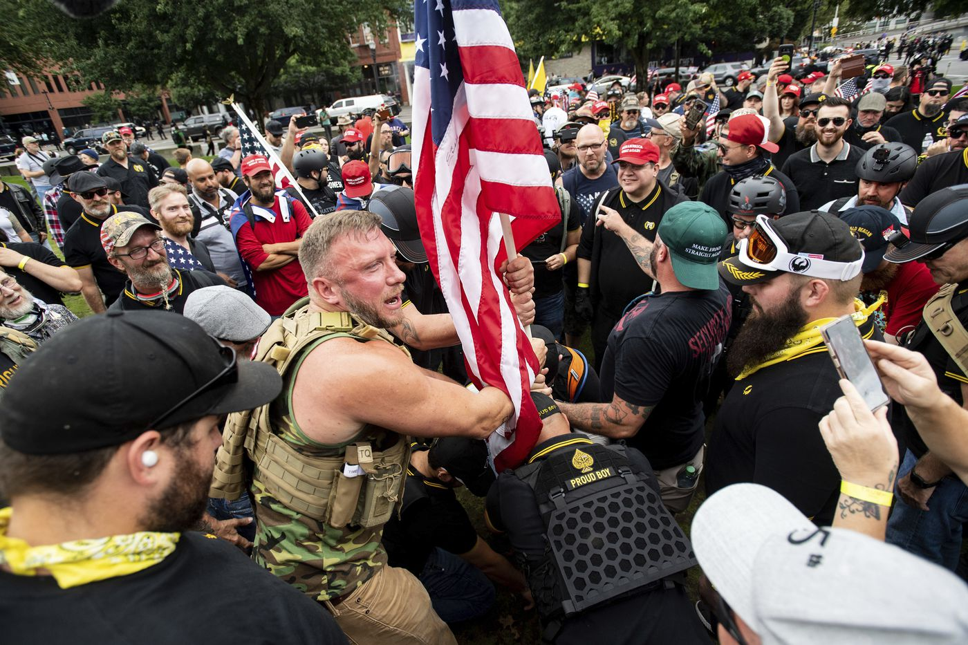 "Joseph Oakman and fellow Proud Boys plant a flag in Tom McCall Waterfront Park during an ""End Domestic Terrorism"" rally in Portland, Ore., on Saturday, Aug. 17, 2019. Portland Mayor Ted Wheeler said the situation was ""potentially dangerous and volatile"" but as of early afternoon most of the right-wing groups had left the area via a downtown bridge and police used officers on bikes and in riot gear to keep black clad, helmet and mask-wearing anti-fascist protesters — known as antifa — from following them. (AP Photo/Noah Berger)<p><br></p>"