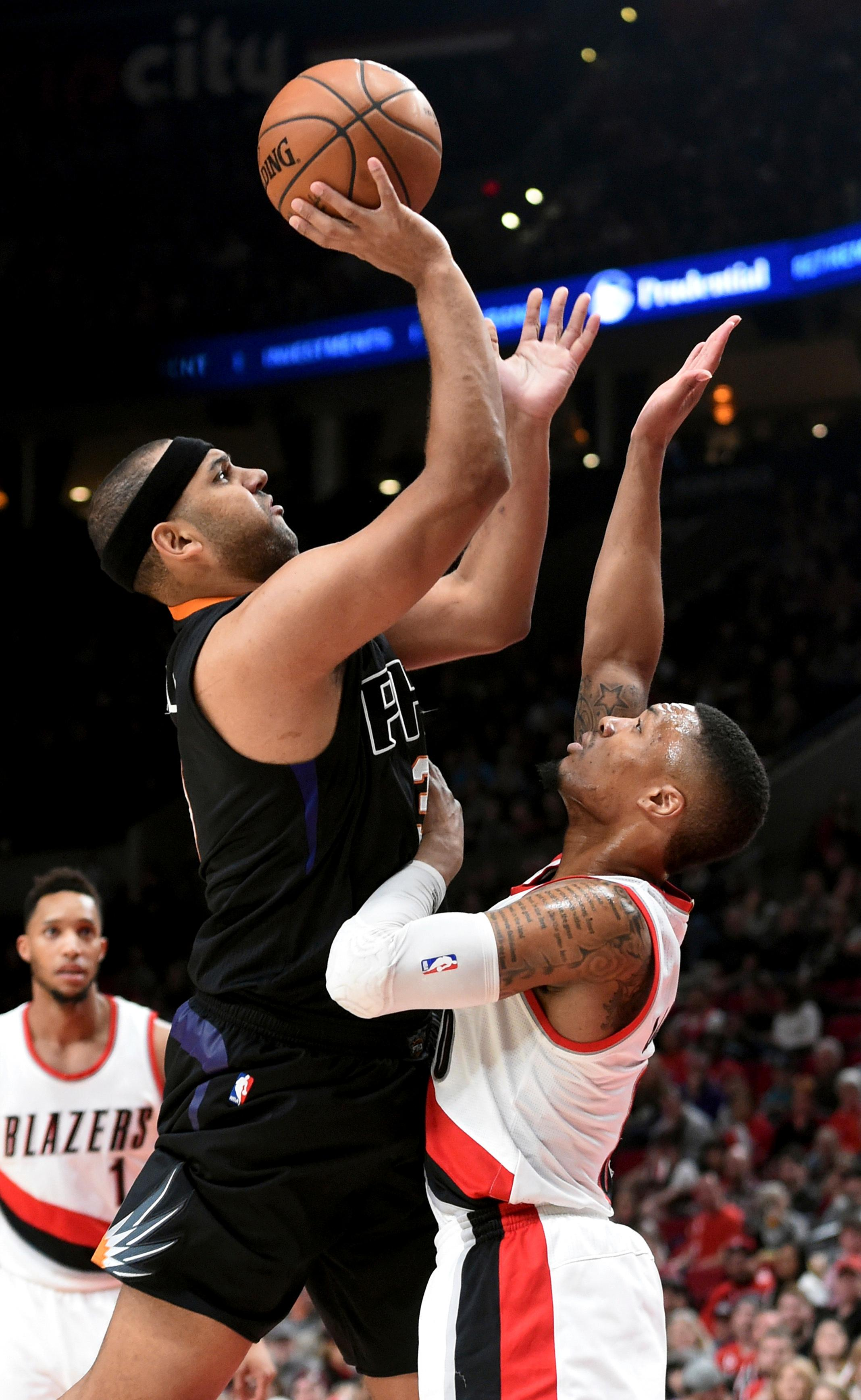 Phoenix Suns forward Jared Dudley shoots over Portland Trail Blazers guard Damian Lillard during the first quarter of an NBA basketball game in Portland, Ore., Saturday, April 1, 2017. (AP Photo/Steve Dykes)